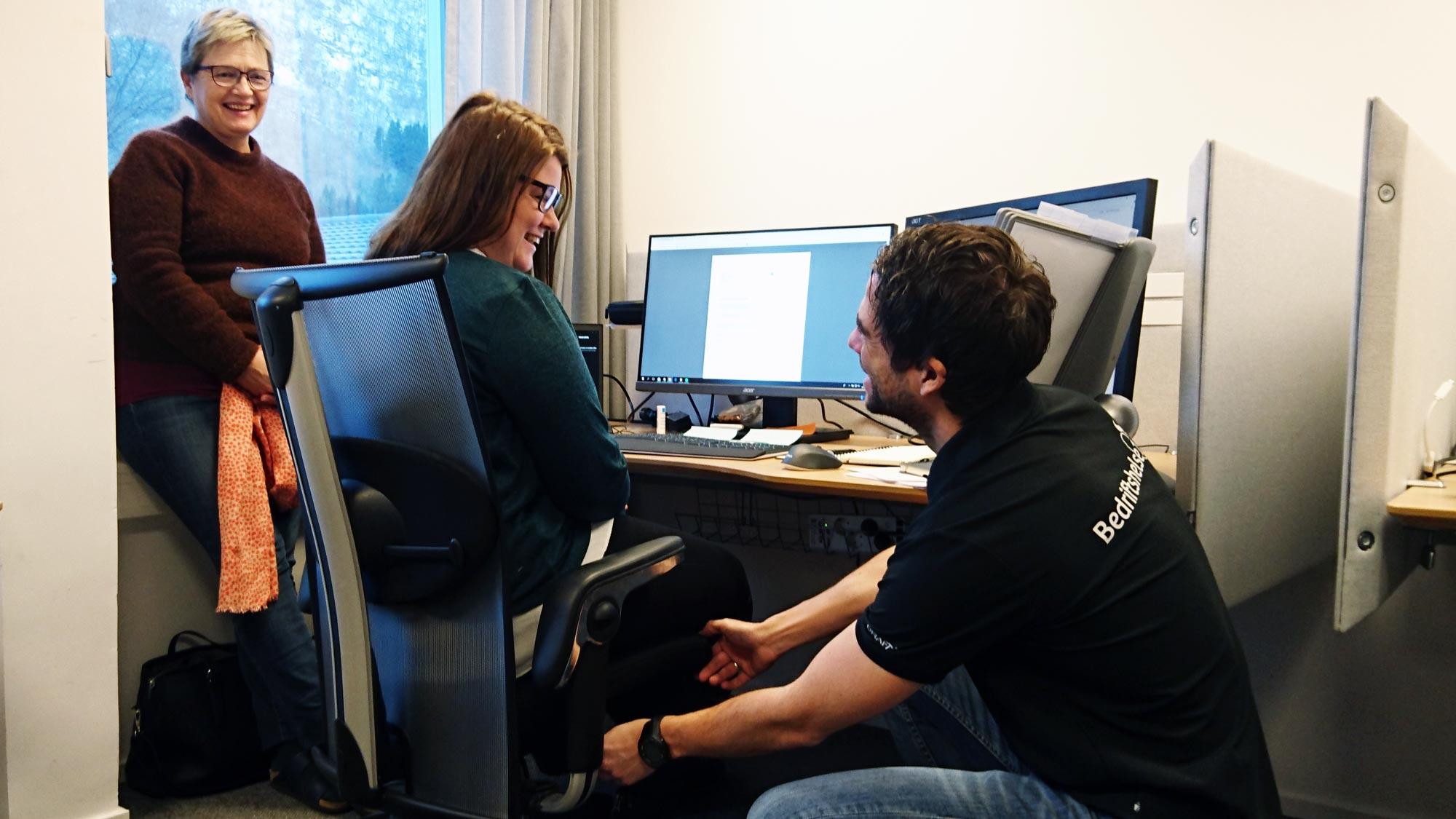 Grethe Hjetland ser at Highsoft-tilsette får hjelp til riktig sittestilling av bedriftsfysioterapeut Anders-Otto Plassen.