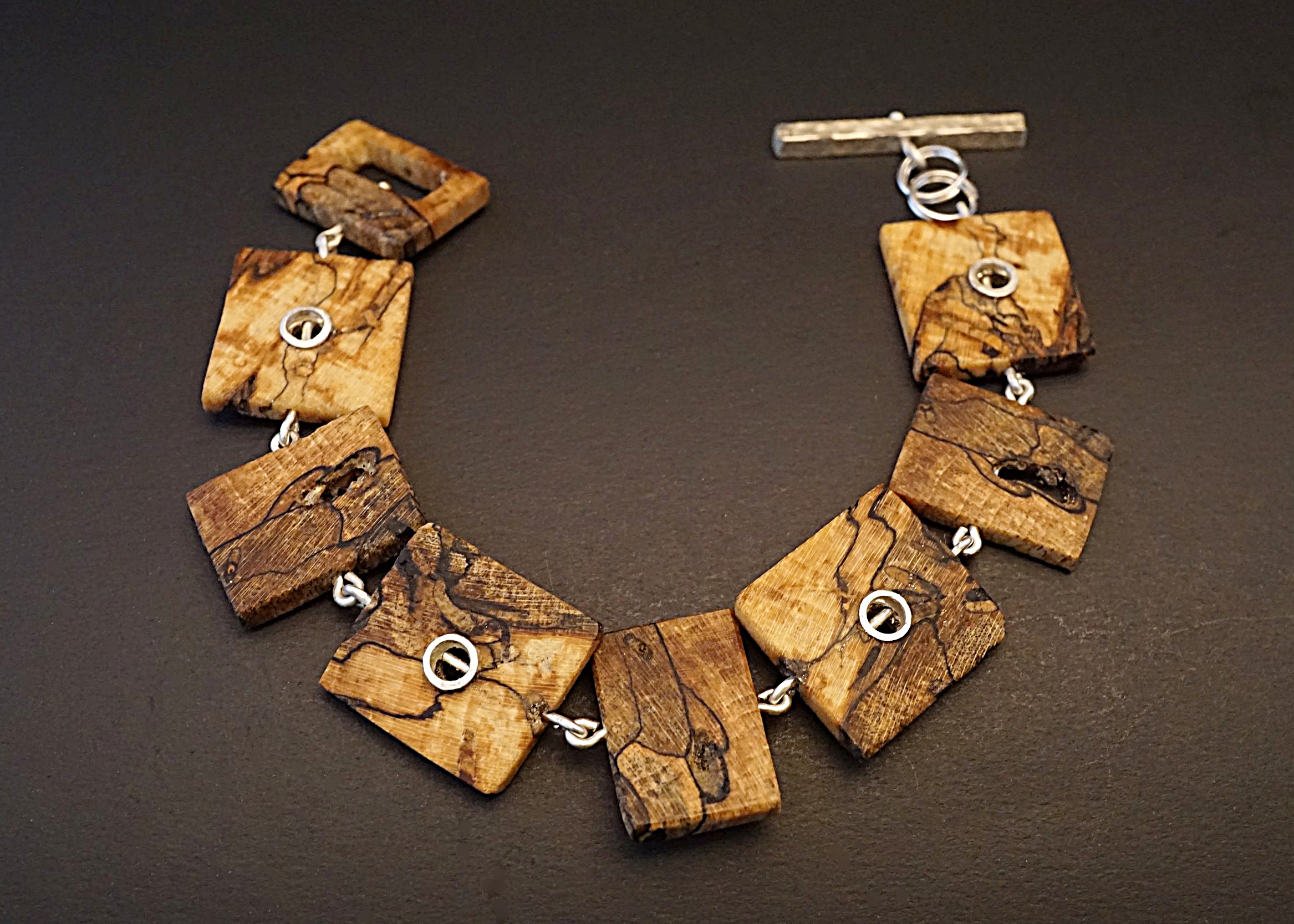 Hand carved northern maple wood links with sterling silver rivets, connector, and toggle