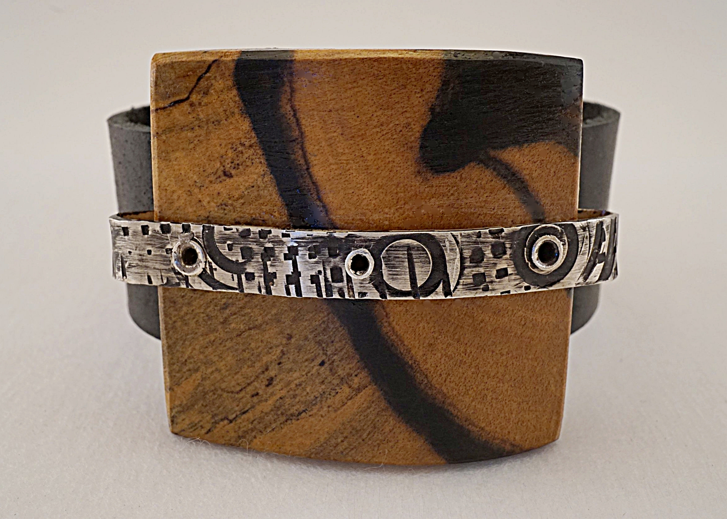 Hand carved black and white ebony wood with hand stamped sterling silver on black leather