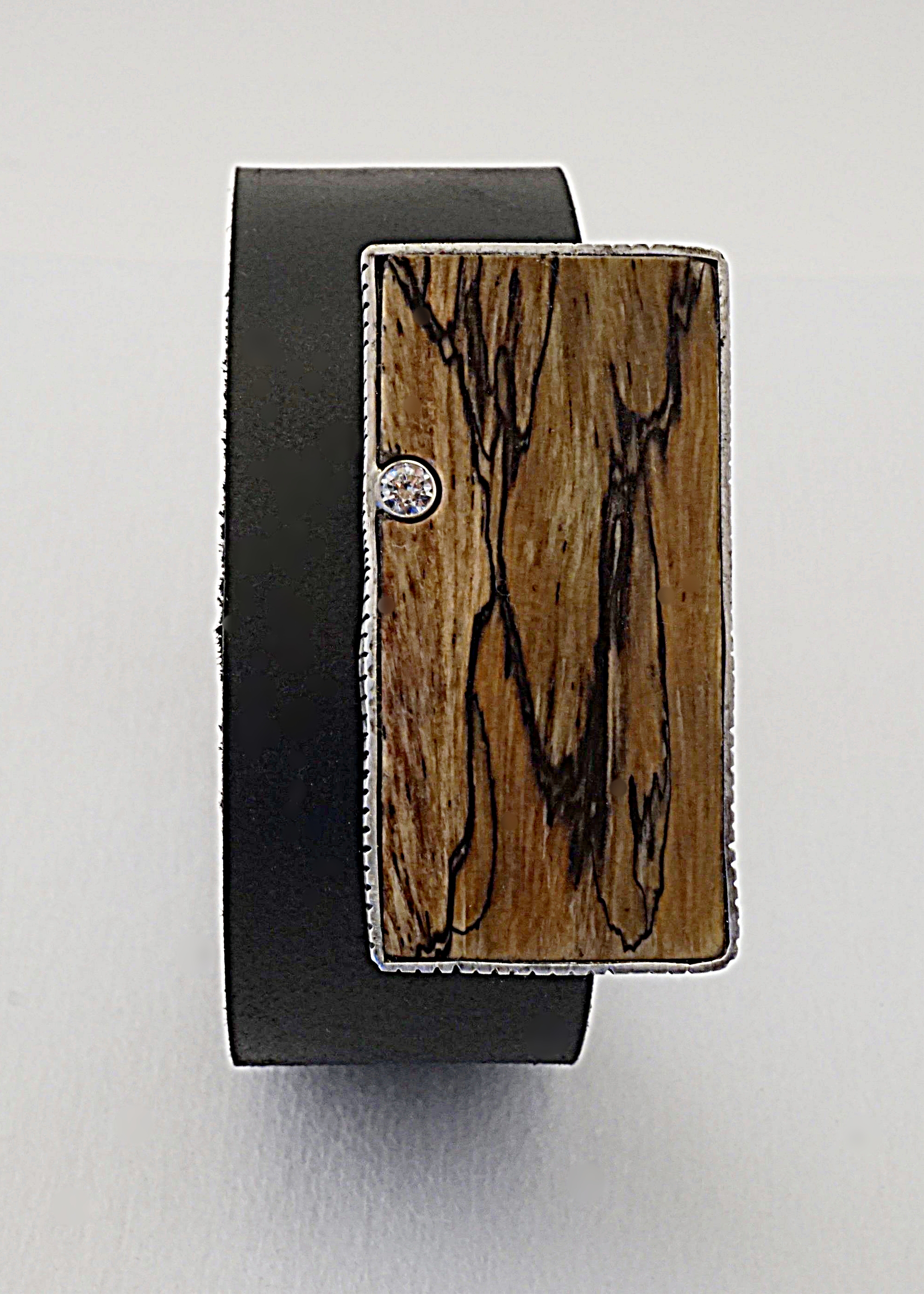 Splated tamarind wood with sterling silver bezel hand textured around wood and sterling silver bezel set with white sapphire on black leather