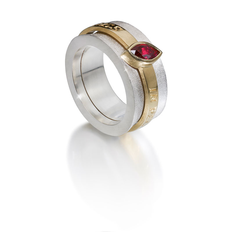 Silver outer ring, 18ct gold inner ring with ruby and engraving in latin 'In the heart I trust'
