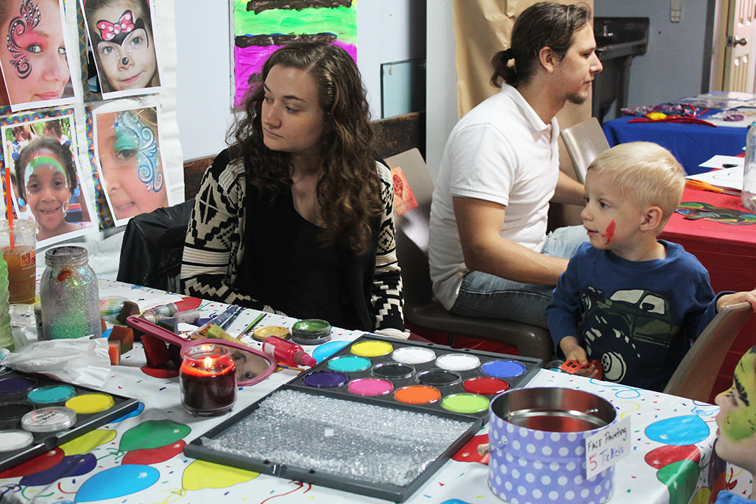 Sarah Damiano showing a young student face painting!