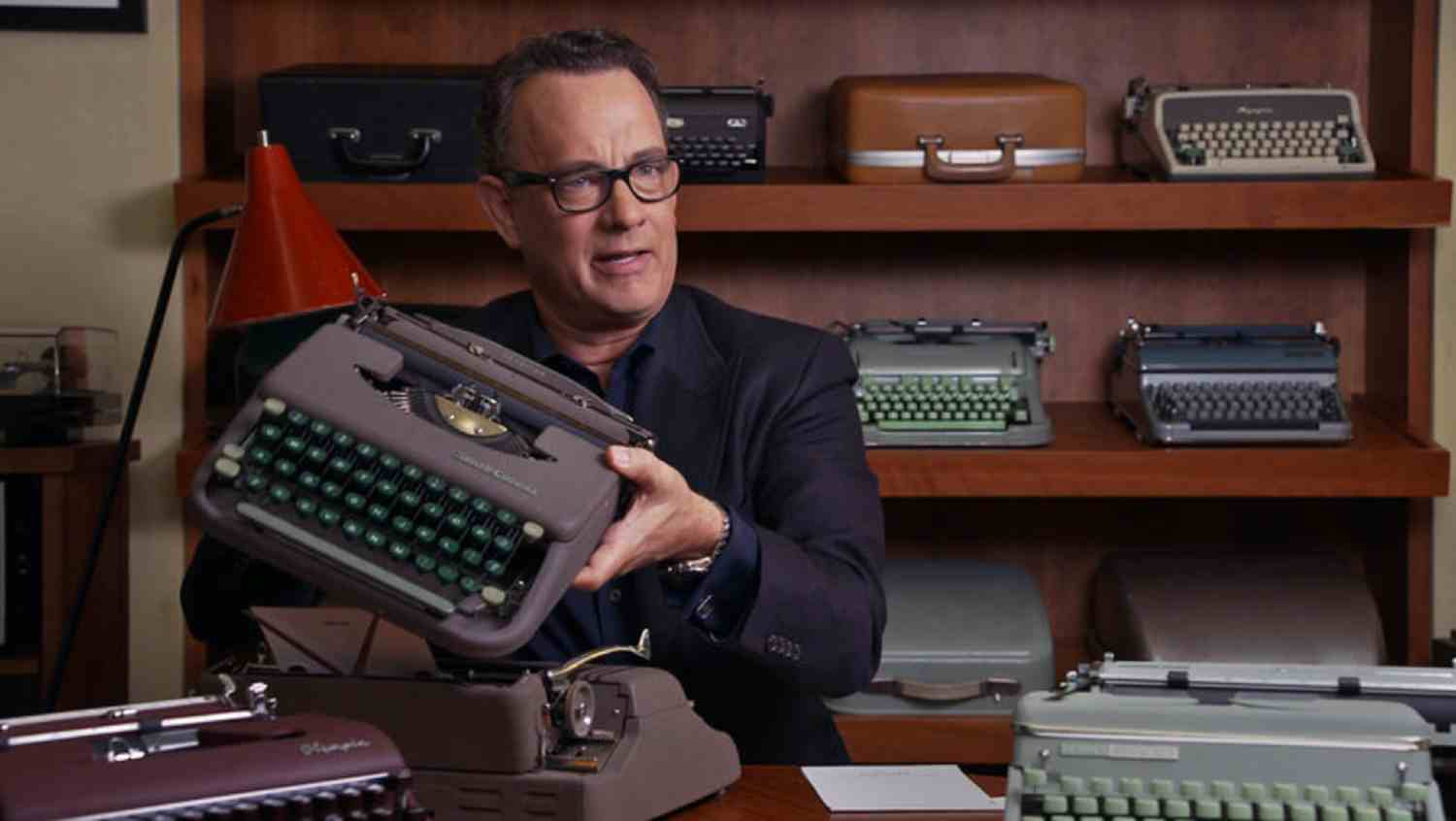 Tom Hanks holds up a typewriter from his collection.