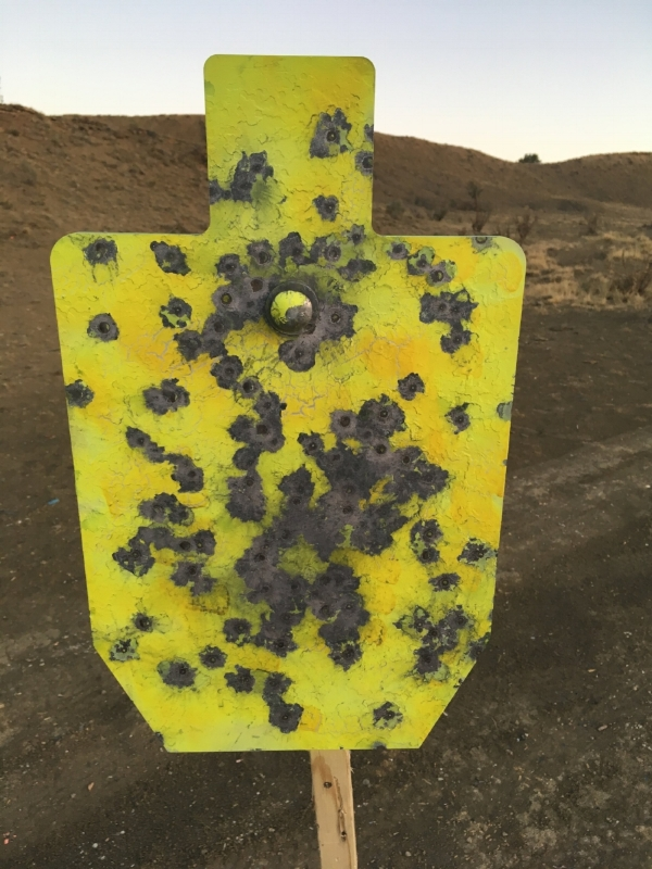 A well-used steel target out in the open country.