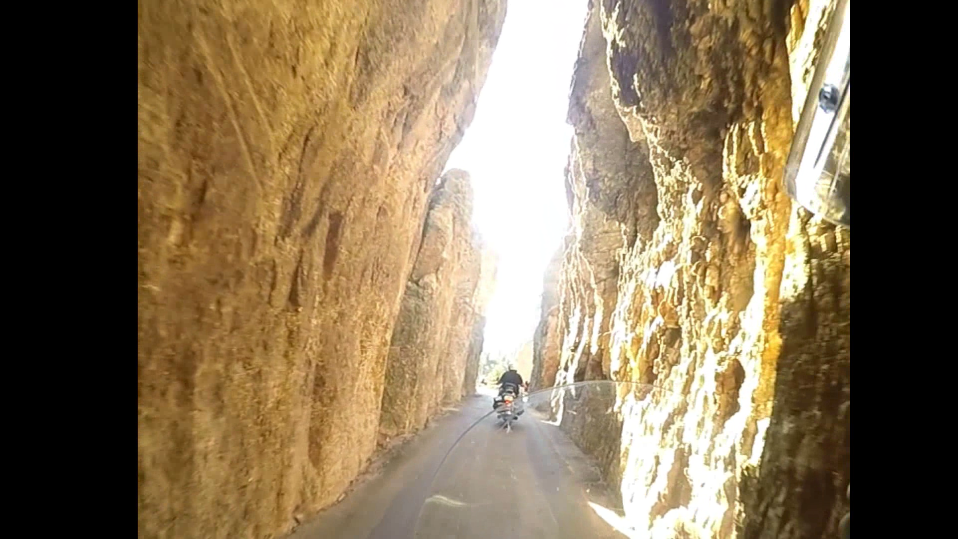 The scenic and curvy Needles Highway comes with narrow tunnels and steep cliff sides.