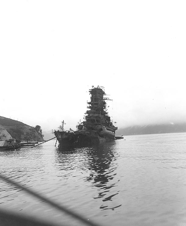 A Japanese battleship sunk at anchorage near Kure harbor. Trees were planted to provide camouflage from high-altitude planes..