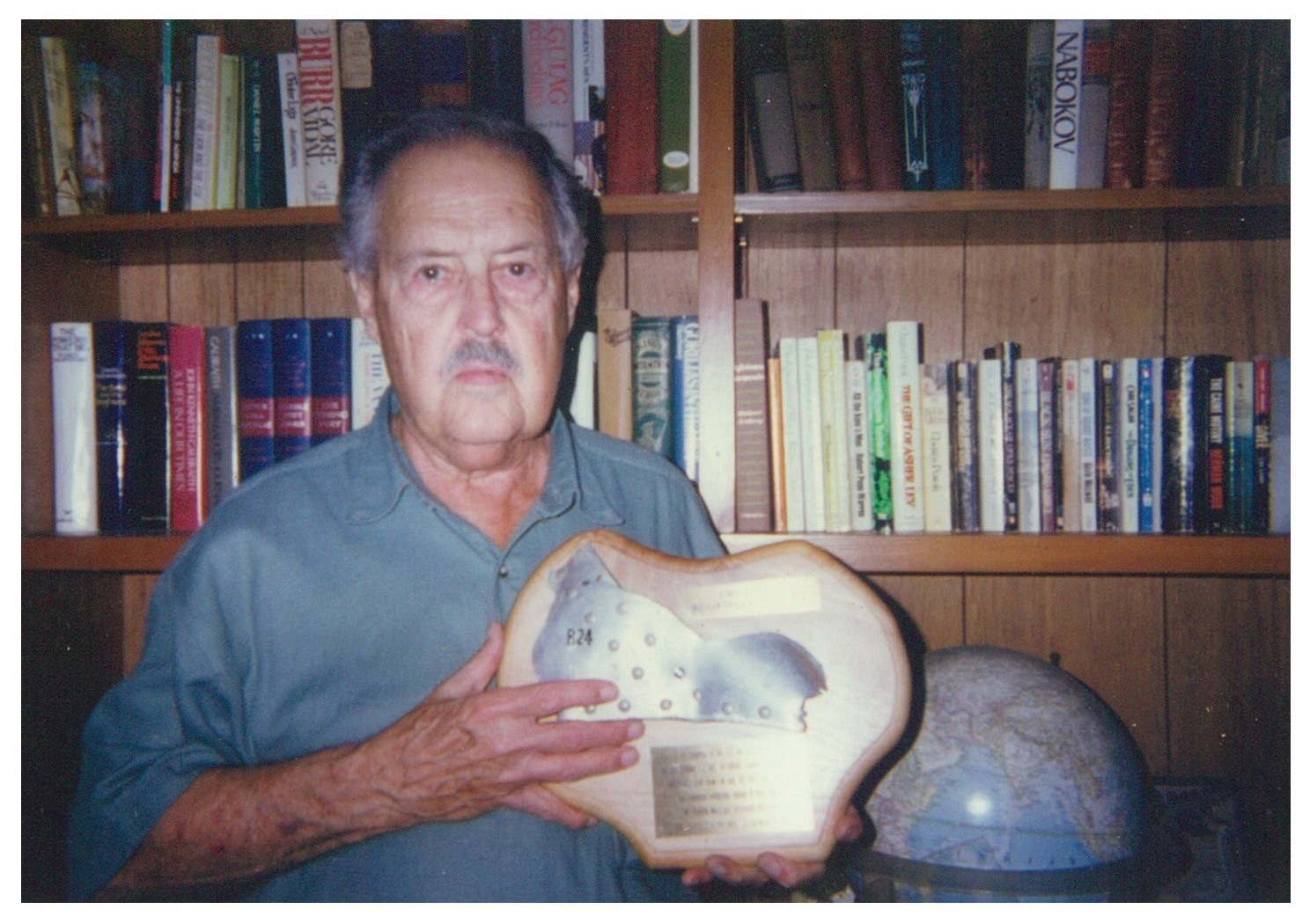 Dr. Cartwright, former pilot-in-command of the  Lonesome Lady , holds the plaque fashioned from a piece of the wreckage from the bomber  Lonesome Lady , sent to him by Mr. Keiichi Muranaka. (Courtesy of Dr. Cartwright.) Professor Cartwright was profoundly moved by receiving this fragment of the plane that he commanded as a 21-year-old 2nd Lt. in the US Army Air Force.