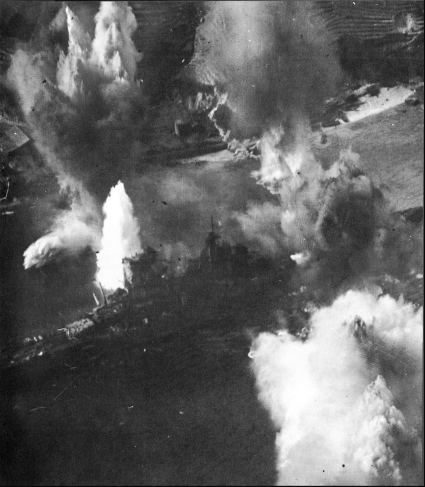 The stern of the  Haruna  appears to be struck by a bomb while other bombs and torpedos explode, as well.