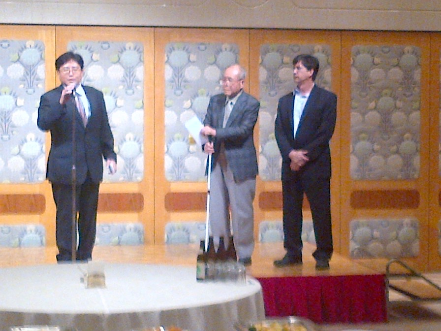 Radiation Effects Research Foundation (RERF) Reception in Hiroshima in which Shigeaki Mori was recognized for his work and his experience as a hibakusha (atomic bomb-affected person). Japanese Space Agency Flight Surgeon, Yu Koike, provided an introduction in Japanese while Mr. Mori and Mark Shavers look on. October, 2014.