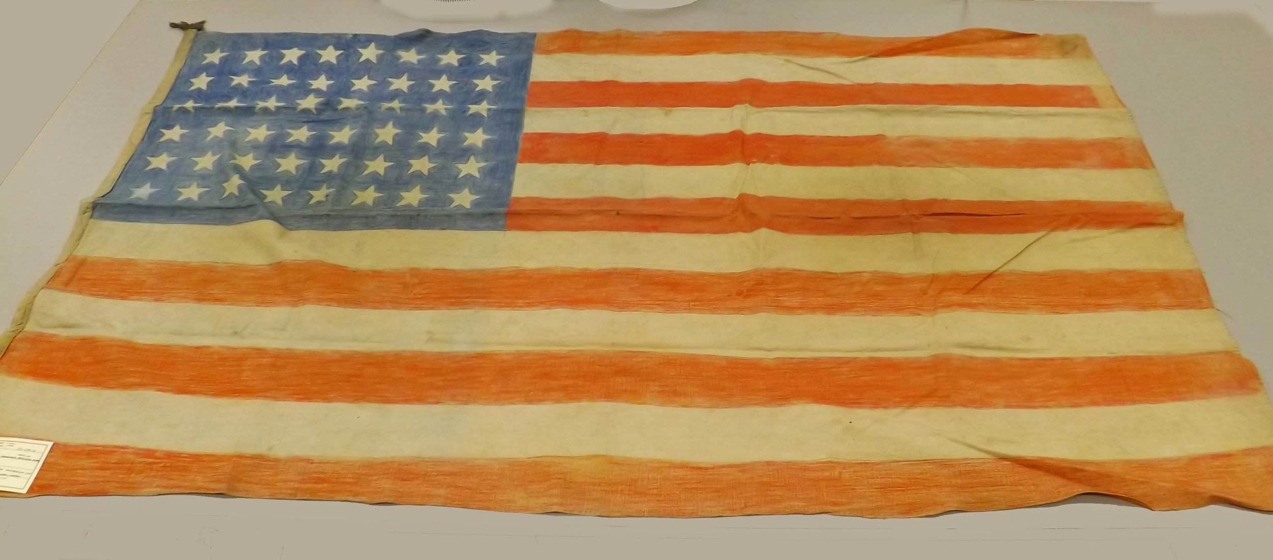 James D. Landrum carried the U.S. flag in these photos. The flags were carefully created by the POWs using bedsheets and colored pencils and were a tremendous symbol of pride for these men, some who were regaining their freedom after three years and eight months working at hard labor under deplorable conditions.