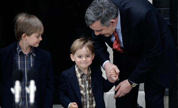 Former PM Gordon Brown holds the hand of son Fraser in 2010 - four years after The Sun put his medical condition on its front page