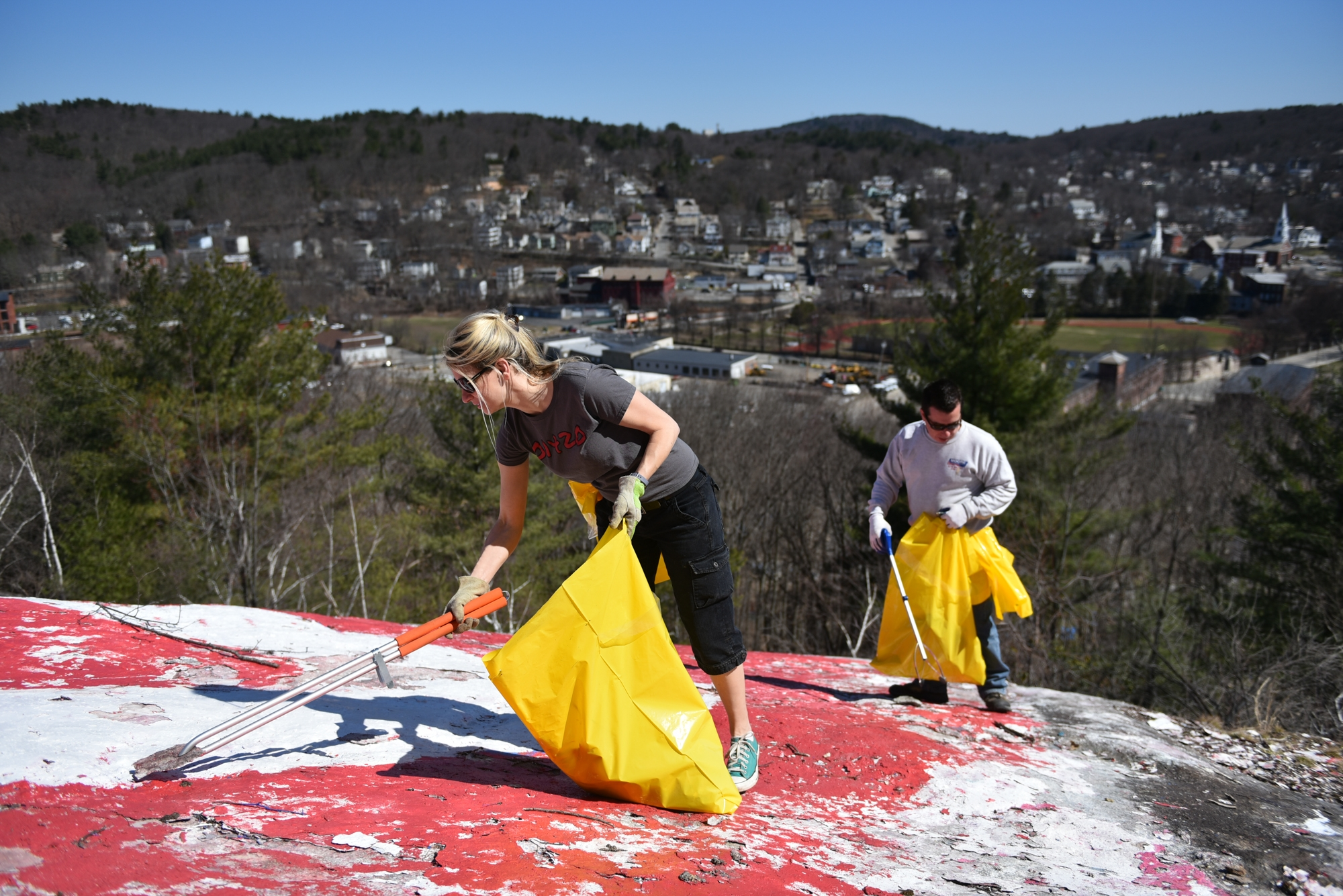 Community Leaders Sam Squailia and Joe Bowen gather loose trash on Rollstone Hill rock on Sunday is celebration of Earth Day.