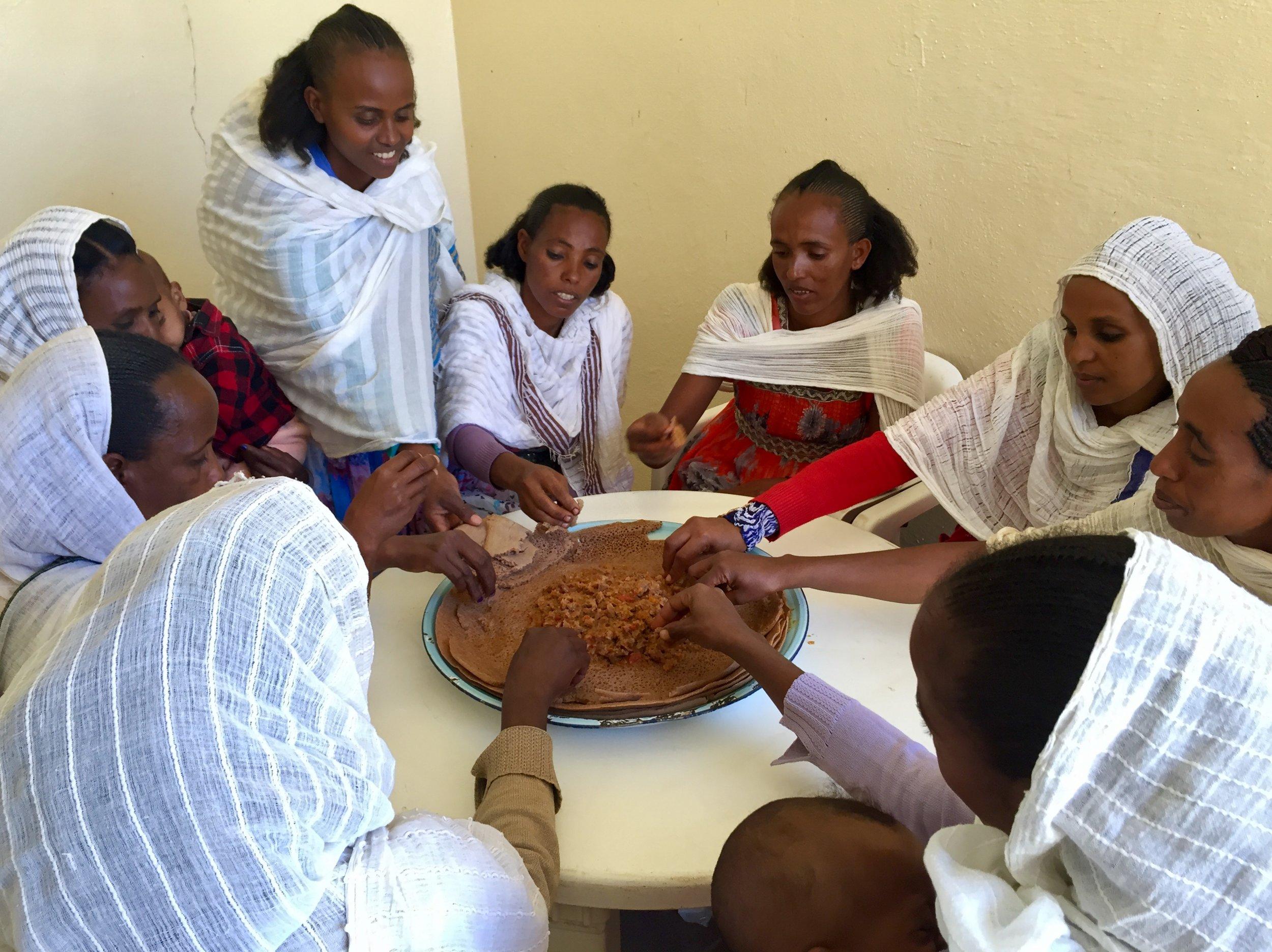 Rahwa team members eating injera.