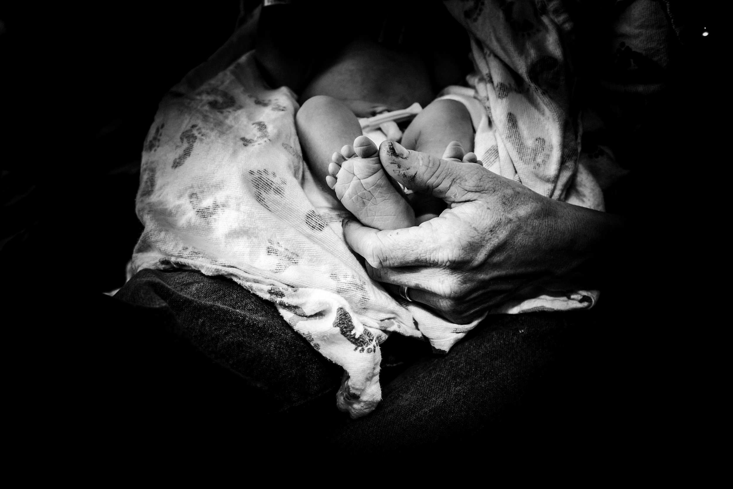 Black and white image of newborn baby's feet in daddy's hands