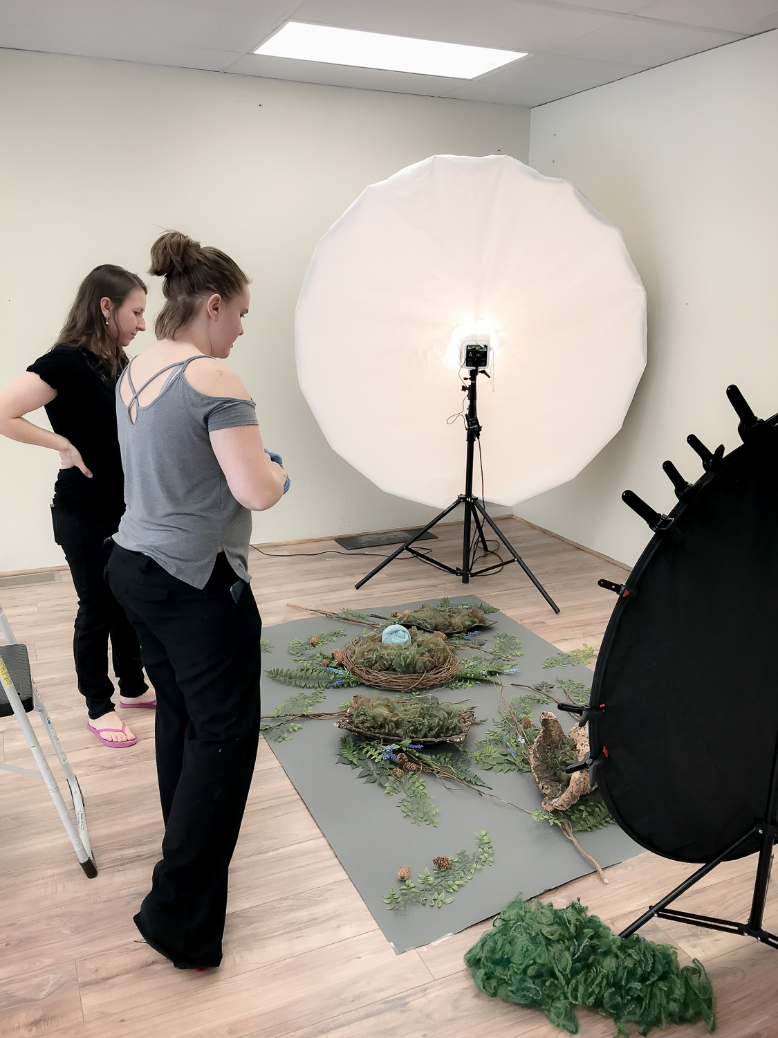 Photographer and assistant laying out a forest backdrop with studio light in the corner