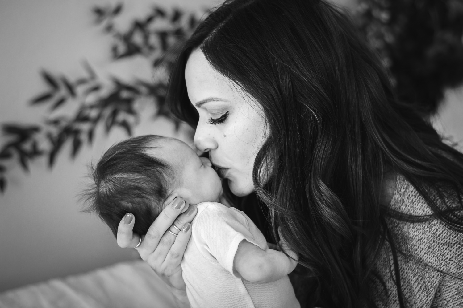 Black and white image of mommy kissing her newborn baby boys face.