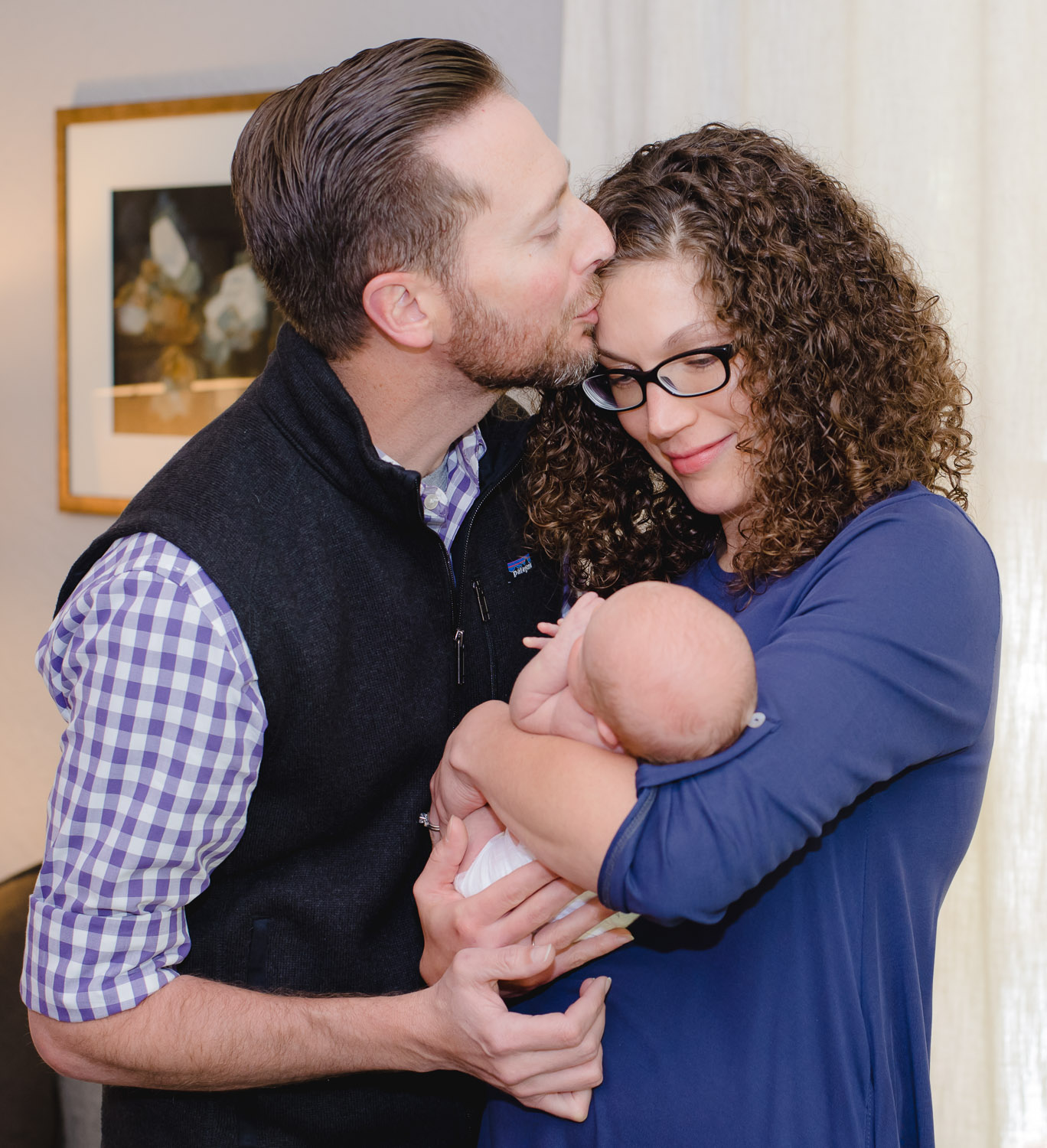 Husband giving a big kiss to his wife on her forehead while she is holding their newborn daughter.