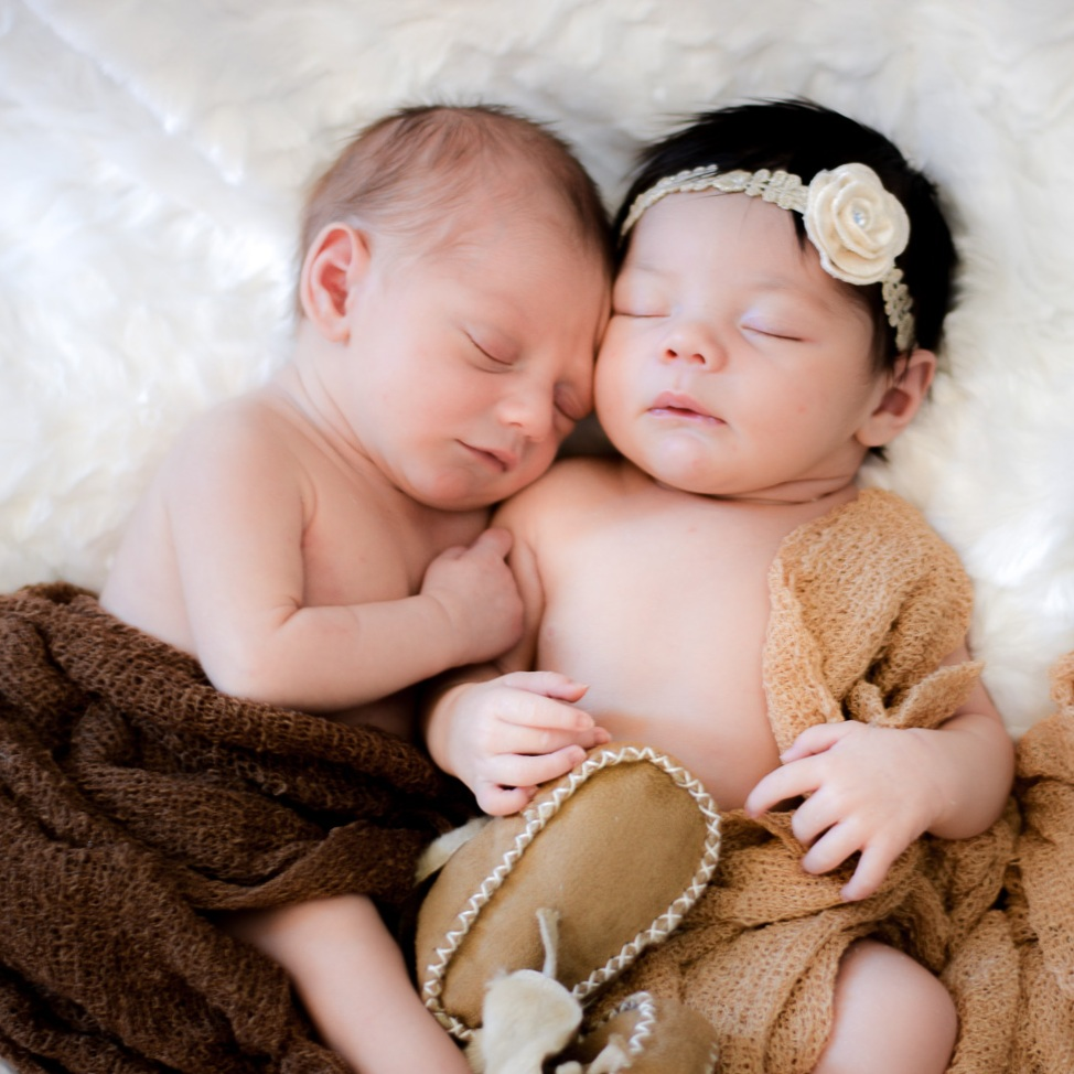 Two newborns snuggling together.