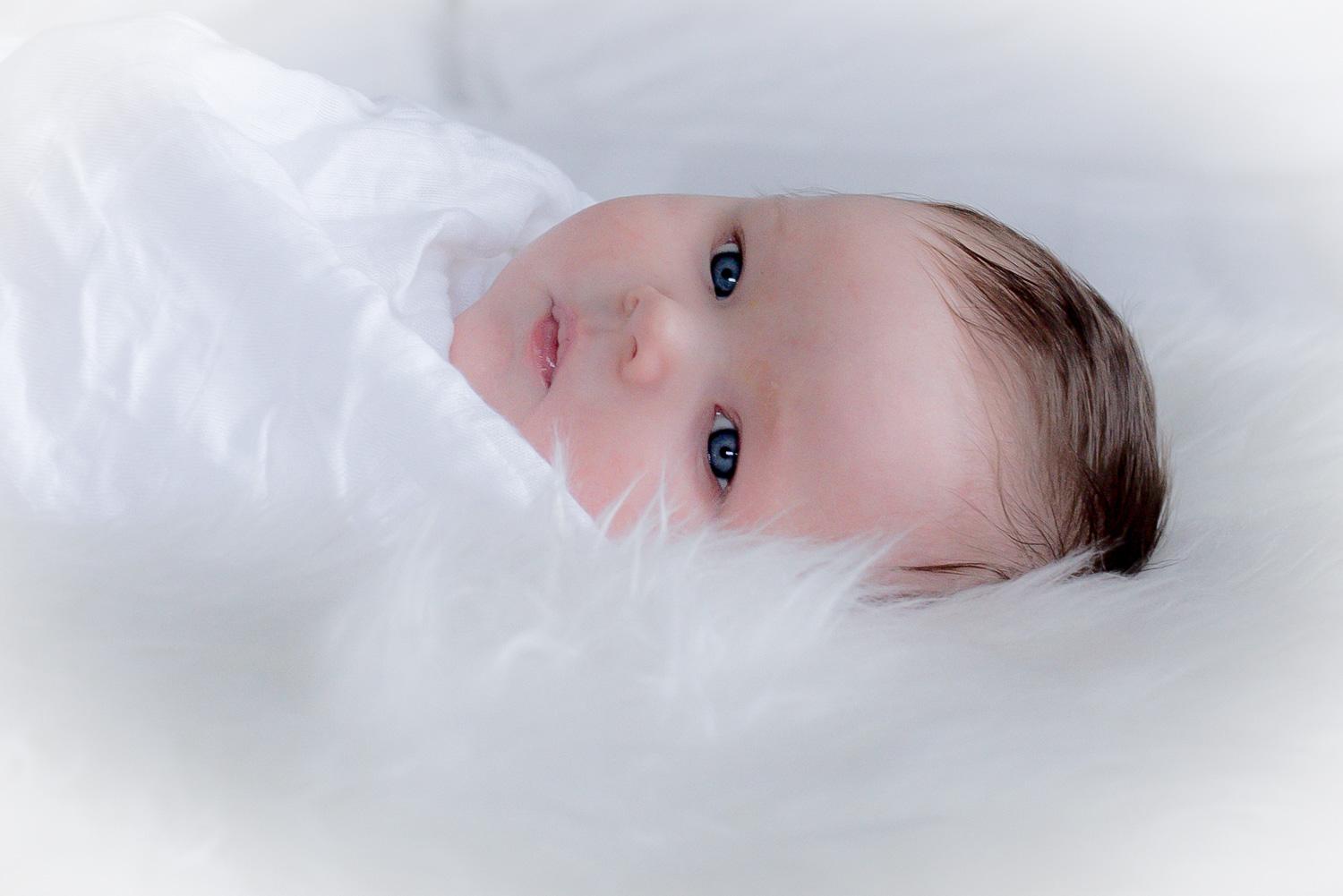 Newborn baby wrapped in soft white blanket ready for a nap.