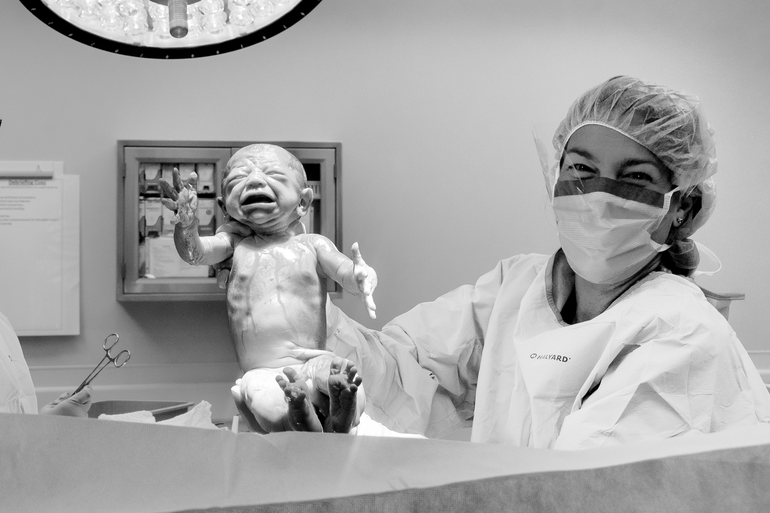 All birth is beautiful. Black and white image of doctor holding up newborn delivered via Cesarean.