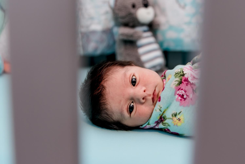 Baby peeks through the rails on her cri.