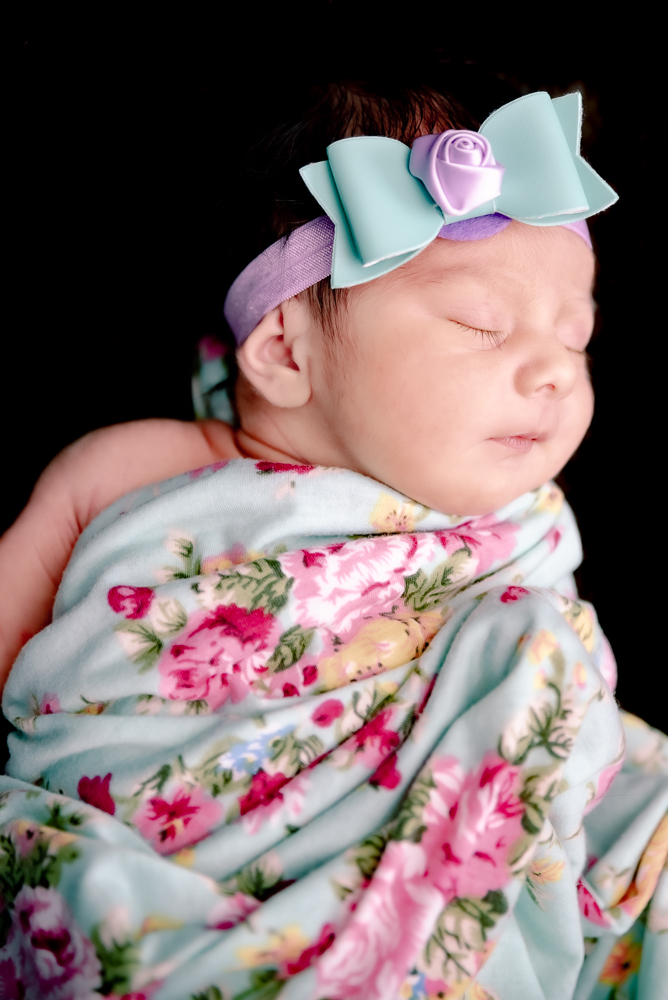 Beautiful baby girl swaddled in blanket while she sleeps