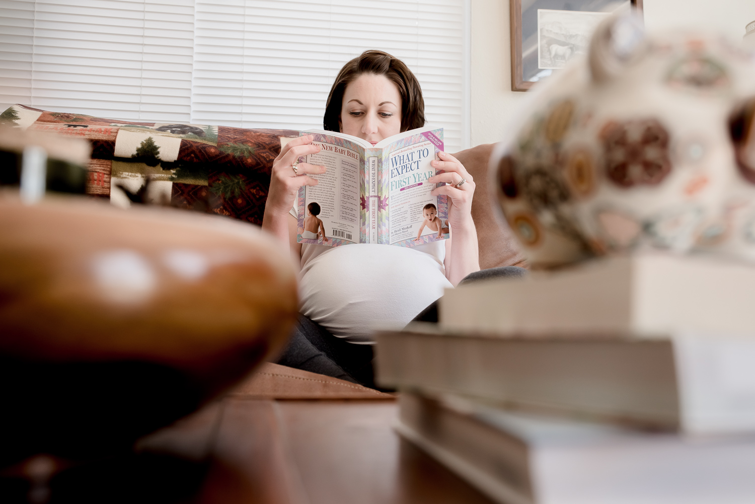 Expecting mommy reads What to Expect When You are Expecting while sitting in her living room. Larimer County Colorado