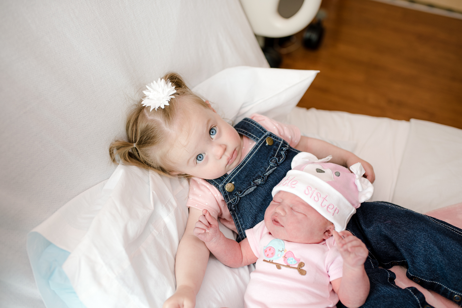 Sweetest big sister ever, holding her new baby sister.