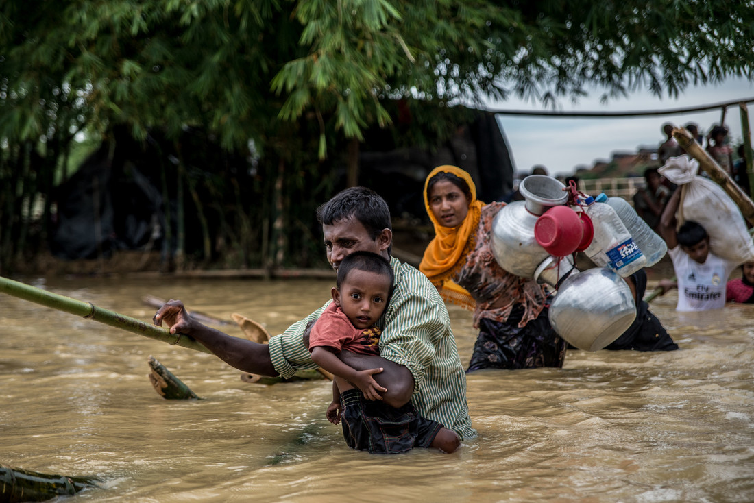 Photo:  Aurélie Marrier d'Unienville  / Oxfam   - A father carries his son across a broken bamboo bridge on the edge of Balukhali camp, Bangladesh. Rains flooded many of the temporary shelters, forcing refugees to move to higher ground.