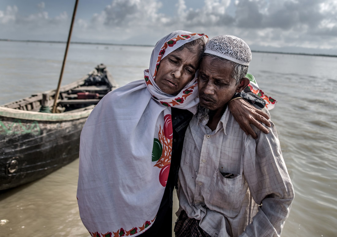 Photo:  Aurélie Marrier d'Unienville  / WaterAid - A Rohingya refugee carries his wife, who suffers from tuberculosis, ashore on the Teknaf peninsula, Bangladesh; after crossing the Naf River which borders Myanmar and Bangladesh.
