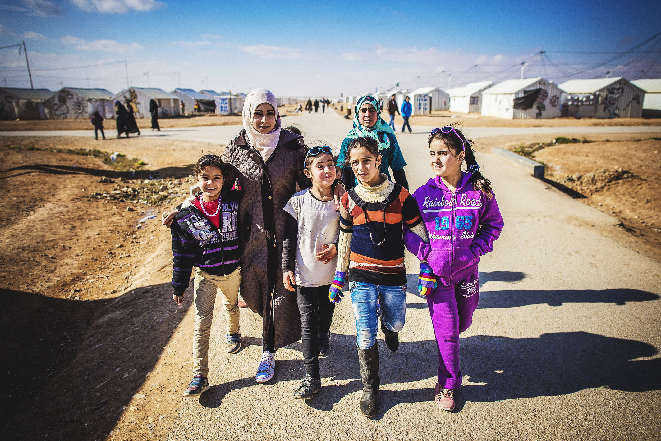 photo:  Sean Sheridan  for Mercy Corps, Azraq refugee camp for Syrians, Jordan. Yasmin, 21, a facilitator at Makani Center (a youth safe place) escaped Syria after her family's home in Daraa was bombed. She is pictured here with refugee children who attend the center in order to have a safe place to play and retain a valuable sense of routine.