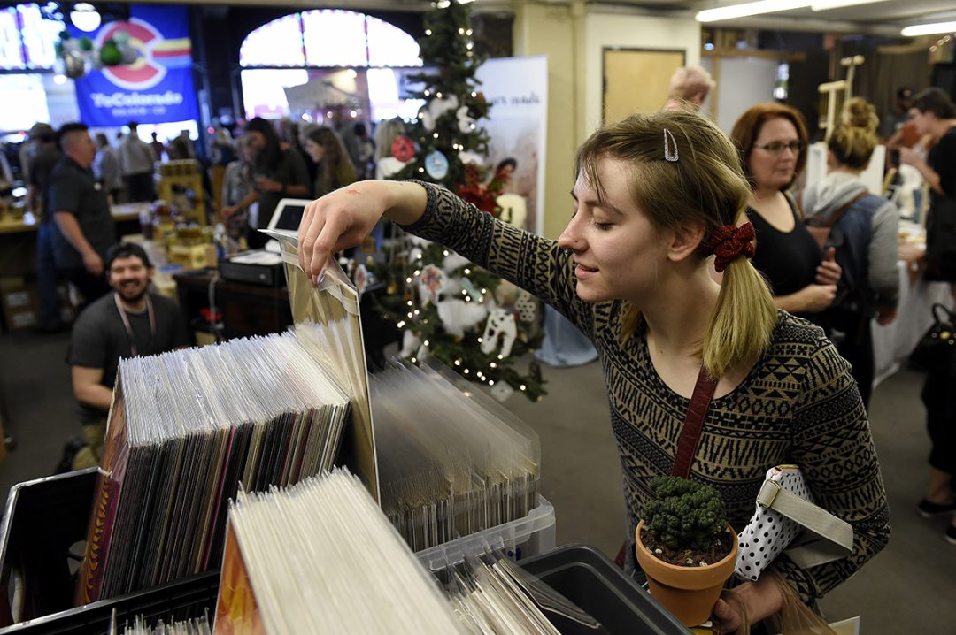 Julia Johnson checks out art prints at the Arsenal Ware booth during the Denver Holiday Flea at Sports Castle on November 2, 2017 in Denver, Colorado. (Seth McConnell, Special to The Know)