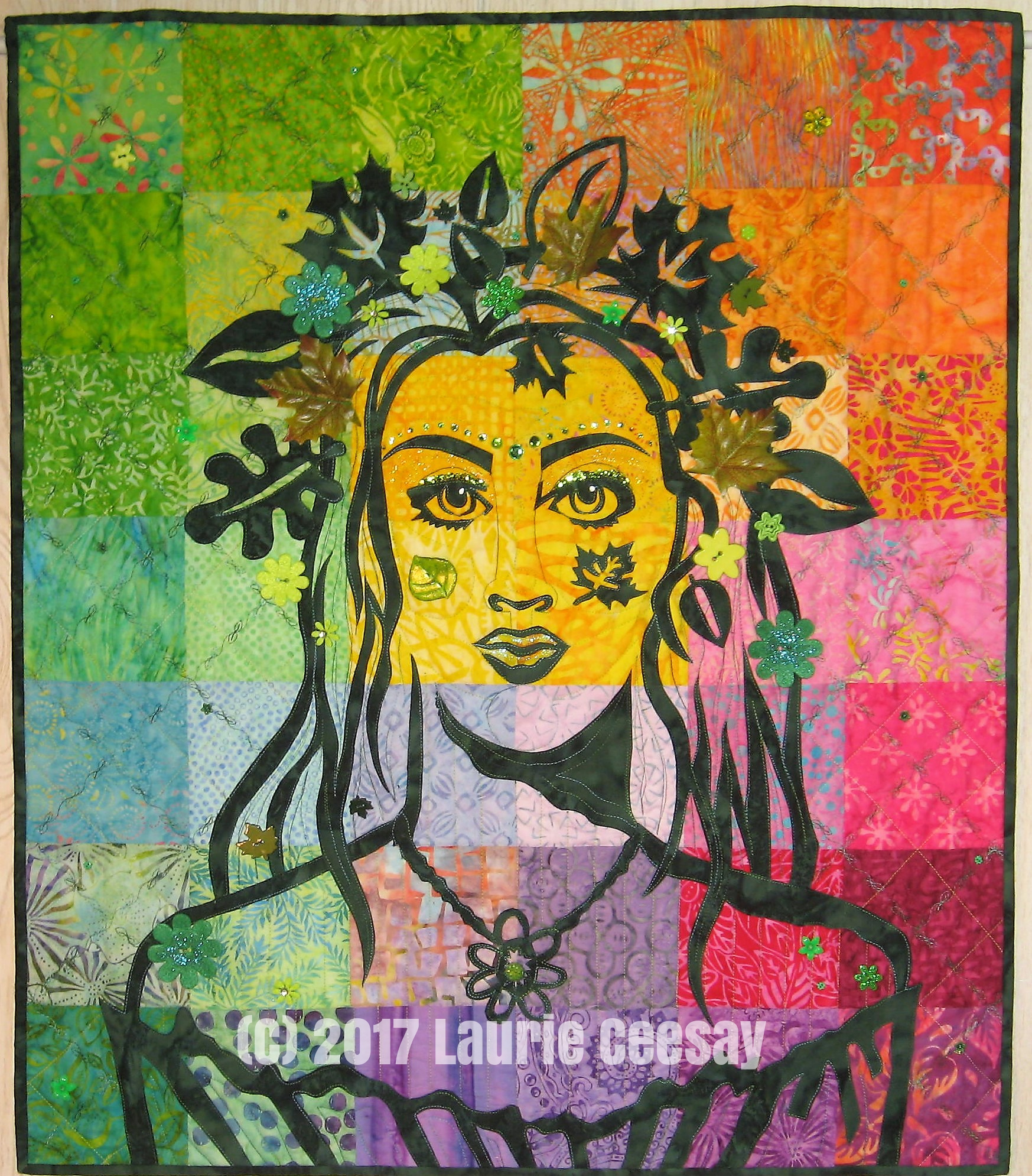 """This is my newest portrait quilt pattern called """"Earth Mother"""" which is available for sale on my website. I had made this quilt back in 2011 and brought it out of retirement this Spring to show it as examples of embellishment options while lecturing at a quilt show. A few people asked if this was a pattern and I said """"it could be!"""" I changed the background and utilized the piecing of scrappy 5"""" squares to help guide in the applique placement since the vertical and horizontal seam lines work as guidelines.  I selected 42 5"""" squares of batiks for the background and a dark green batik for the raw edged fused applique because green seemed nature-like and Summery. The finished size is 28"""" x 32."""" Earth Mother has long hair, an off the shoulder dress, a pendant necklace and a variety of leaves to form a crown in her hair plus one more on her cheek."""