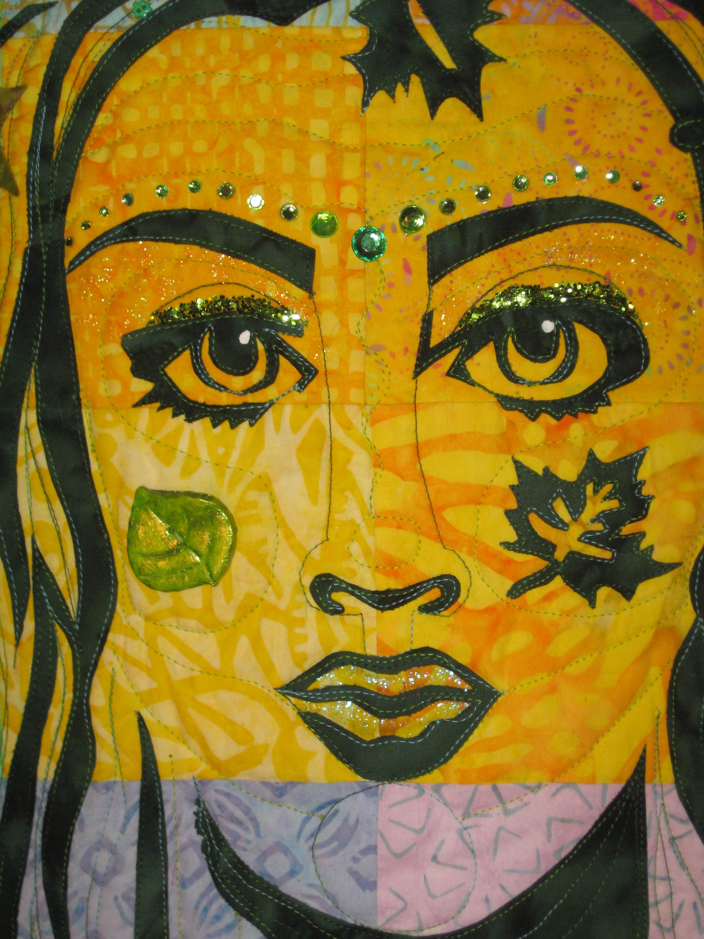 This is the close-up photo of the face with the quilting and the embellishing complete. I pulled from my embellishment stash any leaf or flower, large or small, in a variety of green colors. I added green rhinestones and loose glitter, glitter nail polish and a large glittery bead for the center of the necklace. Lots of sizes of green rhinestones above the eyebrows. The polymer button on the left cheek is painted with green nail polish to shine it up some! I took apart bracelets to use the green beads in this project-anything to have lots of green embellishments!Also silk flower scatter from The Dollar Tree stitched to the quilt in the crown area in between the applique leaves.