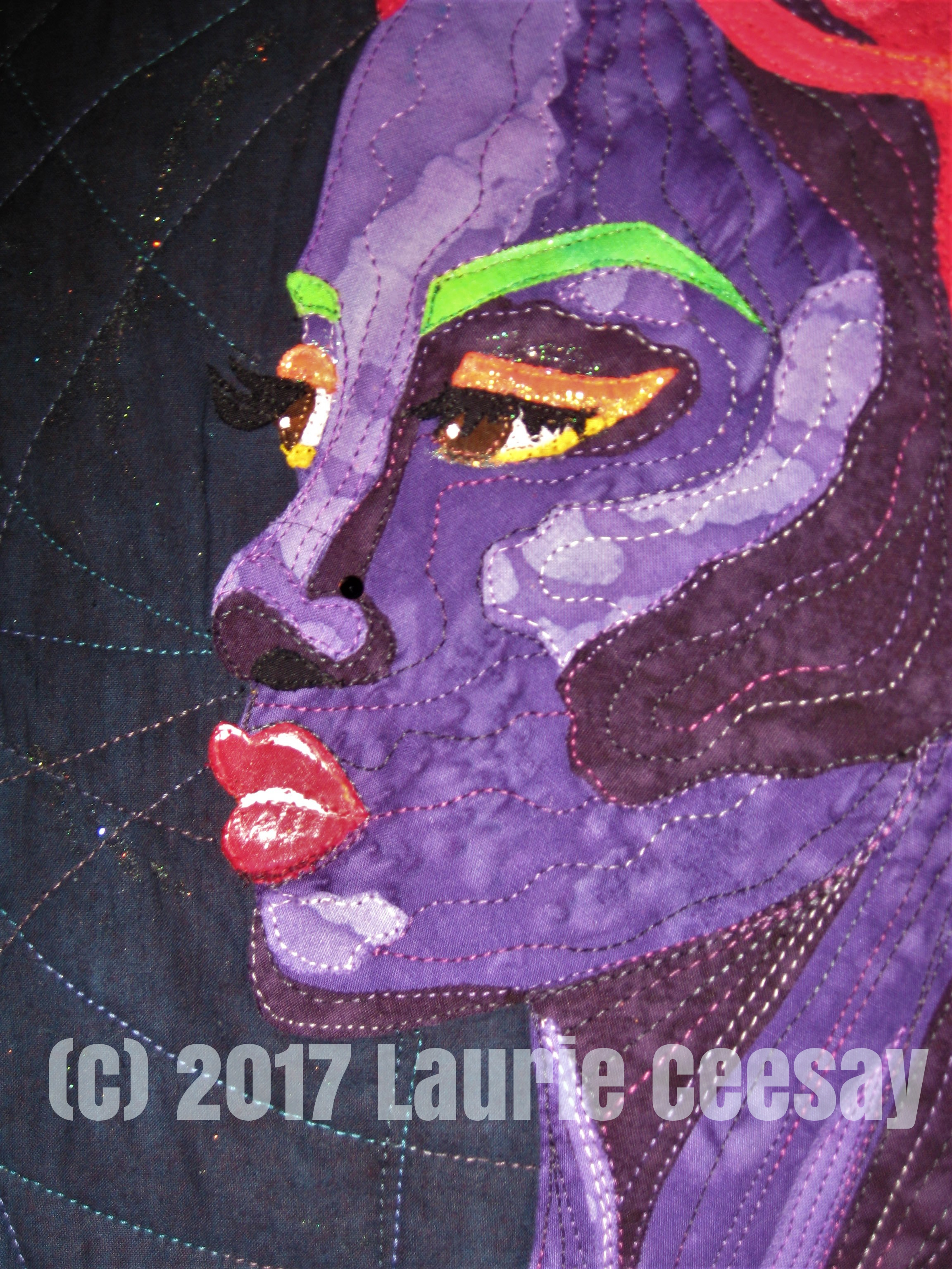 In the close up of the face I added neon loose glitter as eyeliner and a dab of purple glitter poster paint from The Dollar Tree on the eyelids. I used white fabric paint to define the mouth. it is not noticeable in this photo but I used three dark purple beans/sequins for a low contrast color earring and a dark purple rhinestone for a nose piercing. I used some blue glitter nail polish on a small scale to highlight the dark blue background. I quilted large swirly circles which happened thanks to my kitchen! I pulled a large round pizza pan, a large Tupperware lid and a dinner plate to mark the circles! One has to be creative!!