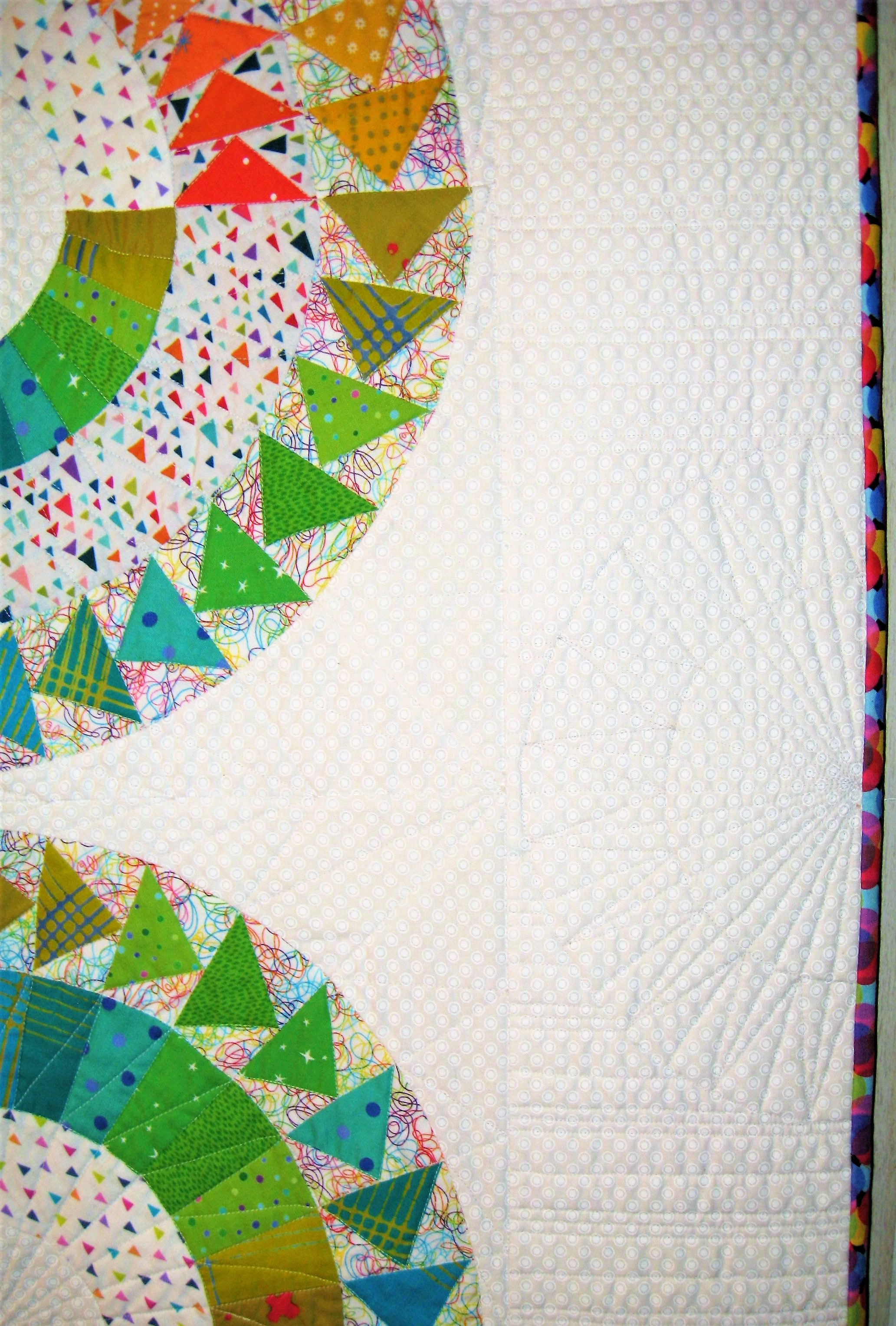 "The quilt was quilted with only white thread. I quilted ""the Hell out of it"" and used 8 bobbins just to quilt it!!  I used a lot of diagonal and radiating lines to quilt the blocks. I added a repeat of the corner New York Beauty blocks in the centers of the outer borders with quilting only then filled in the rest of the borders with a variegated striped effect with stitching. which gave nice texture when the light bounced off of the quilt and created shadows!!  I tacked a small crocheted ""thingie"" which was rainbow colored to the center of the quilt to repeat the color order and bring the four circle blocks together.  The contest is due January 11. 2018 and I have been frantically sewing and quilting on this project between applying for teaching jobs at two major quilt shows, working like crazy in the hair salon in December and doing all the normal Christmas preparations I usually do each year. But it is finished and now I wait until Feb. 2. 2018 to see if it is accepted."