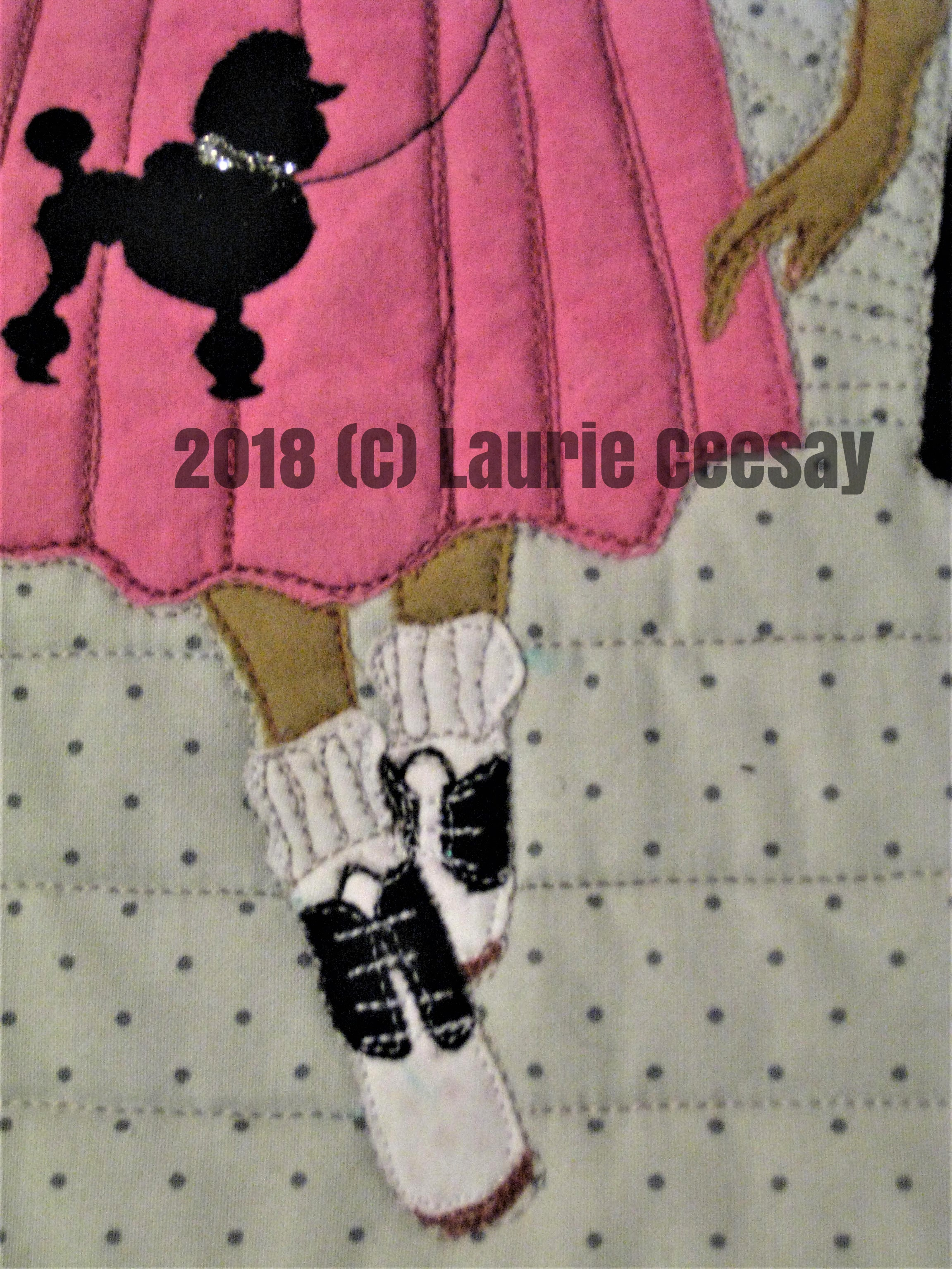 "This is the close-up of the 1950s paper doll. This doll has lots of embellishment including the sweater buttons and the poodle collar/lease.  The 1940s paper doll has fishnet stocking with a back seam, victory roll hair, gloves and pearl jewelry.  The 1950s paper doll has a poodle skirt, bobby socks and saddle shoes, a ponytail and neck scarf.  The 1960s paper doll has Twiggy inspired shift dress and hair, ;ight pink frosty lips and white go-go boots.  The 1970s paper doll has a halter top, wide bell bottom pants and  platform cork bottom sandals.  And the 1980s paper doll has a side ponytail with a scrunchie, leggings and leg warmers and an off the shoulder top wide a wide belt a la Flash Dance!  I had a great time making this mini quilt. I probably should get out my seam ripper to remove the personalized ""K"" on the 1950s sweater."