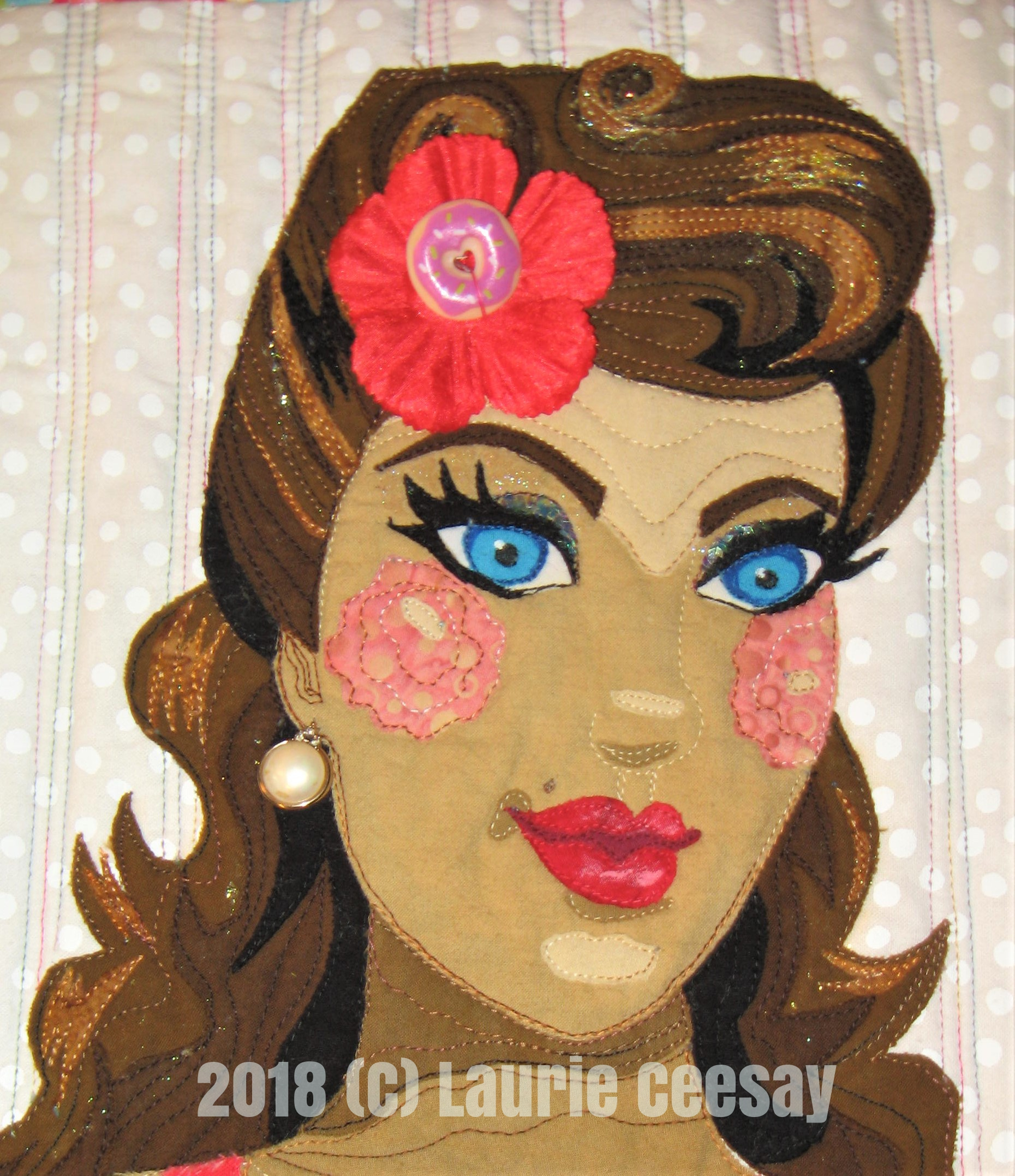 In the face detail the use of glitter nail polish is used in the hair and brow bones. Chunky turquoise glitter is applied to the eye lids. A red flower from a dollar store Hawaiian lei with a cute donut button from Joann Fabrics in the center adds pin up vintage flair!. I sewed donut buttons to the four corners of the quilt as well. I used a vintage earring of my Mother's for Betty's earring.