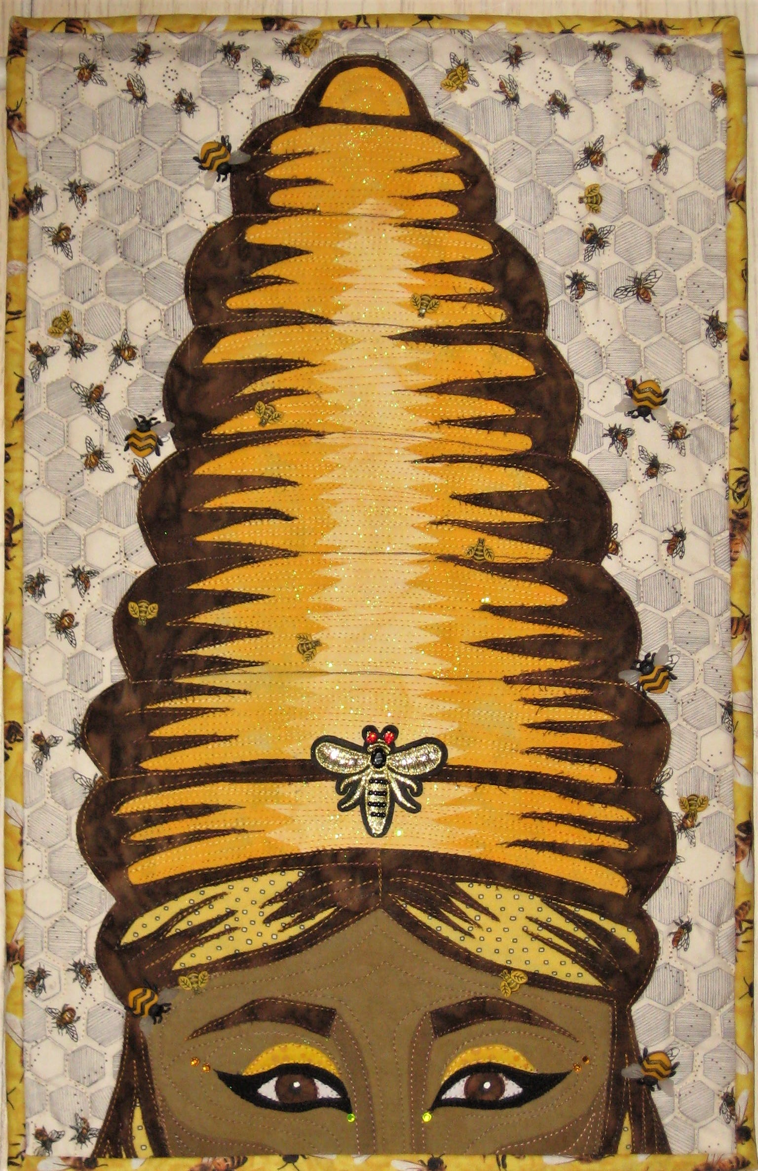 Today is reveal day for my Facebook art quilt group Art Quilts Around The World. The theme is BUGS and I chose bees as my bug of choice for two reasons. First, I have a refrigerator magnet with a woman wearing a bee hive hairstyle with bees swarming around her head and, second, I remembered a 2008 movie based on the book The Secret Life of Bees by Sue Monk Kidd. The story is about 3 black women who are sisters in the 1960s who live on a farm and are bee keepers. They run a honey business and their honey is called Black Madonna. Black Madonna represents fertility and motherhood. A white female teenage runaway finds her way to their farm and they take her in. The actresses Queen Latifah, Dakota Fanning, Jennifer Hudson and Alicia Keys are in this movie-check it out!! I love this movie and because of this the woman is my quilt is black.  I Googled to make sure bees are bugs. They are part of the same family of wasps and ants and are know for their pollination abilities.  I chose to take the bee hive idea literal. I found it was easy to find bee themed fabrics and buttons to complete this project.