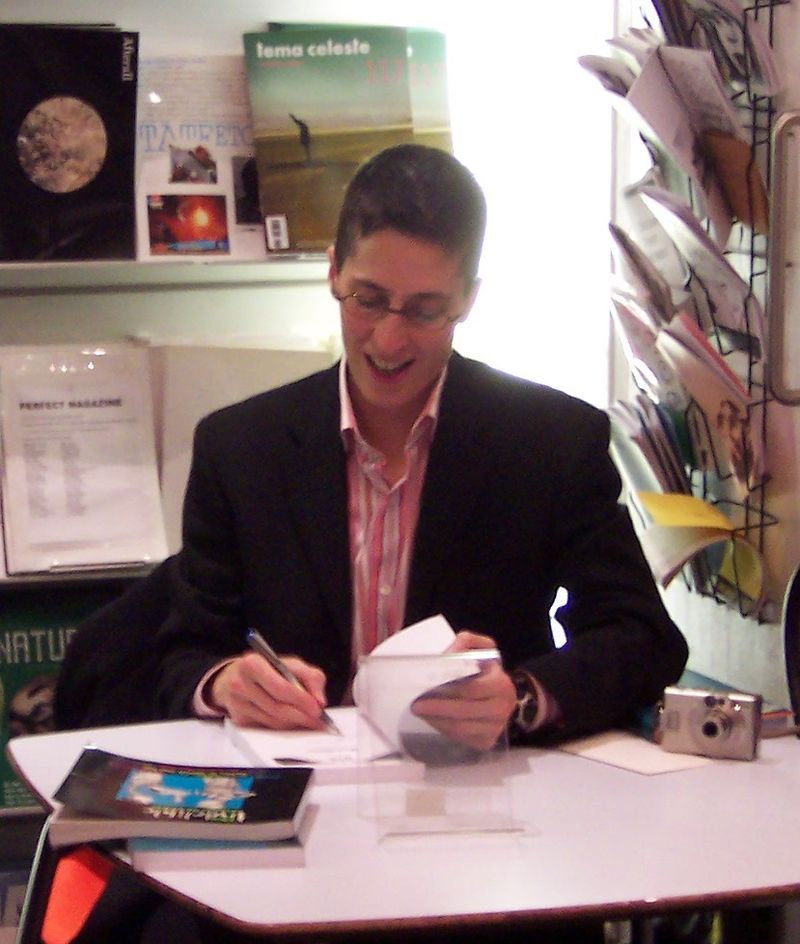 Alison Bechdel at a London signing for Fun Home in 2006  by derivative work:  Josiah Rowe  ( talk )  Fun_Home_Signing_in_ICA_Shop.jpg :  Loz Pycock  -  Fun_Home_Signing_in_ICA_Shop.jpg  is licensed under  CC BY-SA 2.0