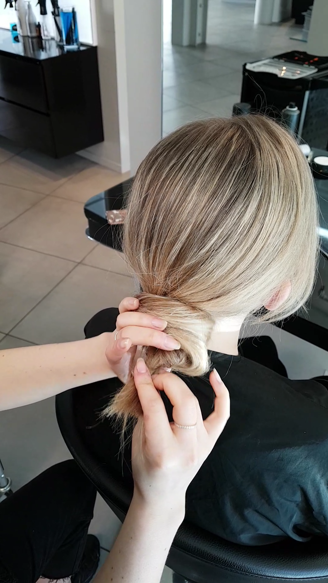 Step 4 - Take the ponytail and twist it around into a knot. Find a shape you like and start to pin the bun into place. To finsh pull out some loose hairs around the face and seal with Label. m Texturizing Volume spray to give a softer natural look.
