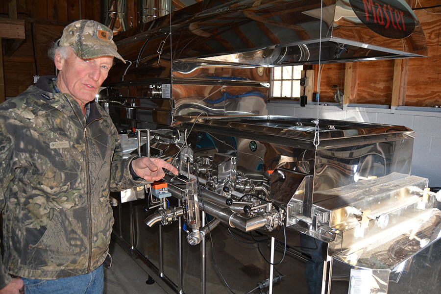 Owner, Roger Bell inspecting the finishing pan before the syrup enters the filter press