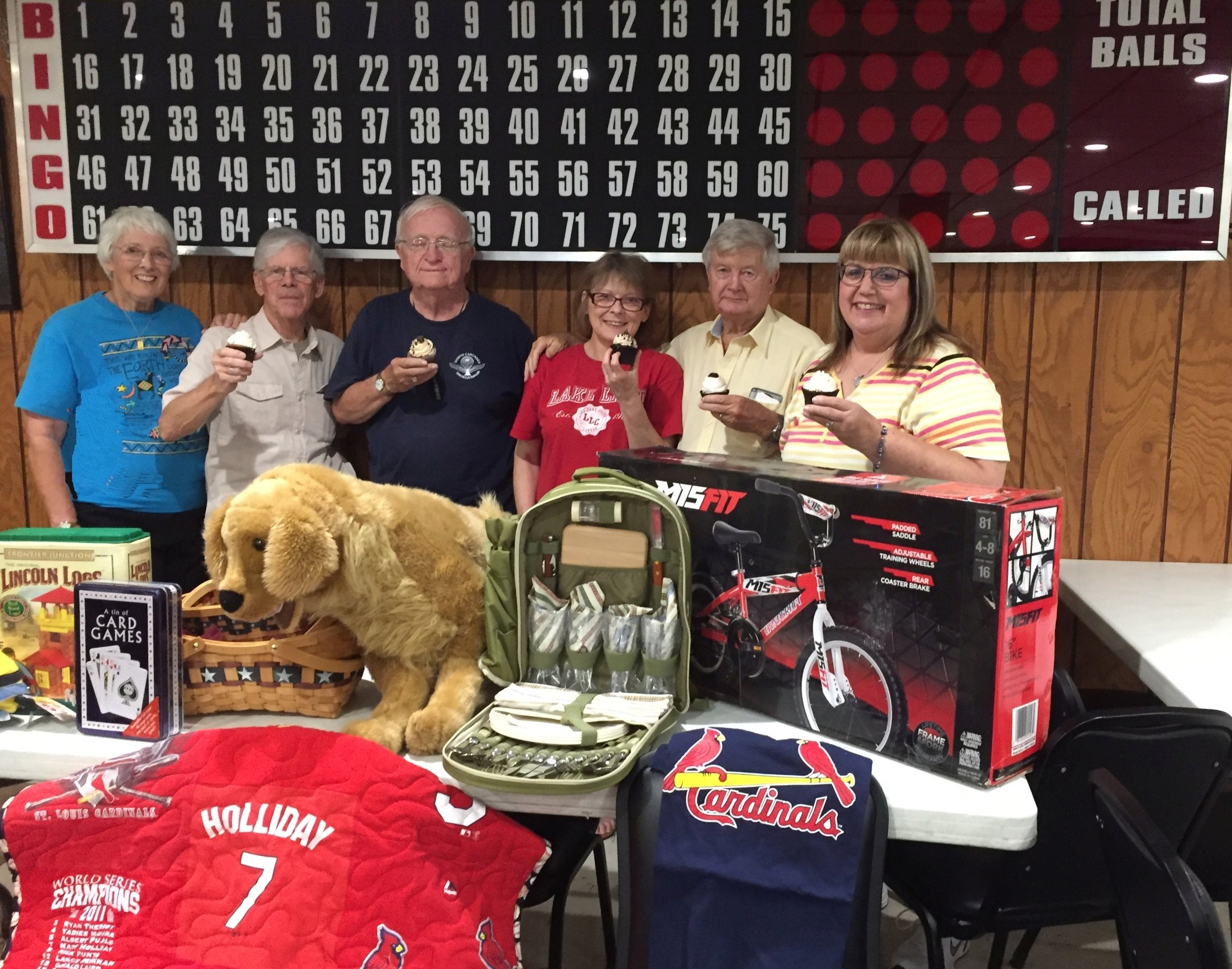 Standing behind the display of bingo prizes and raffle items, with a sweet prize be auctioned off -- cupcakes from Sweet Norma Jean's bakery of Casey, are members of the Five Mile House Foundation board: Kathy Hummel, Tom Vance, Dick Hummel, Giuliana Dongu, Les Dallas, and Karen Jennings.