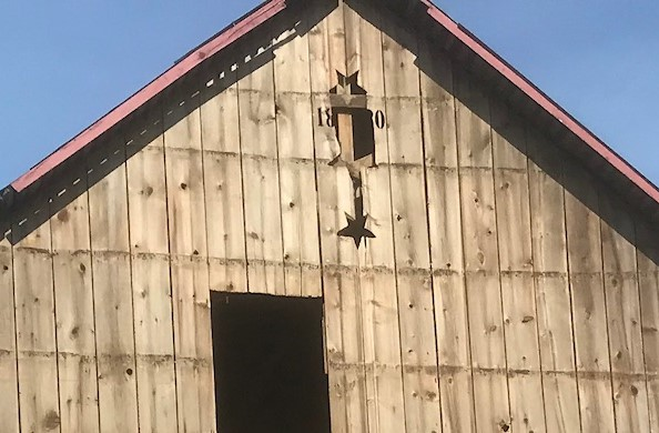 The original barn gable showing three stars and the 1880 date.