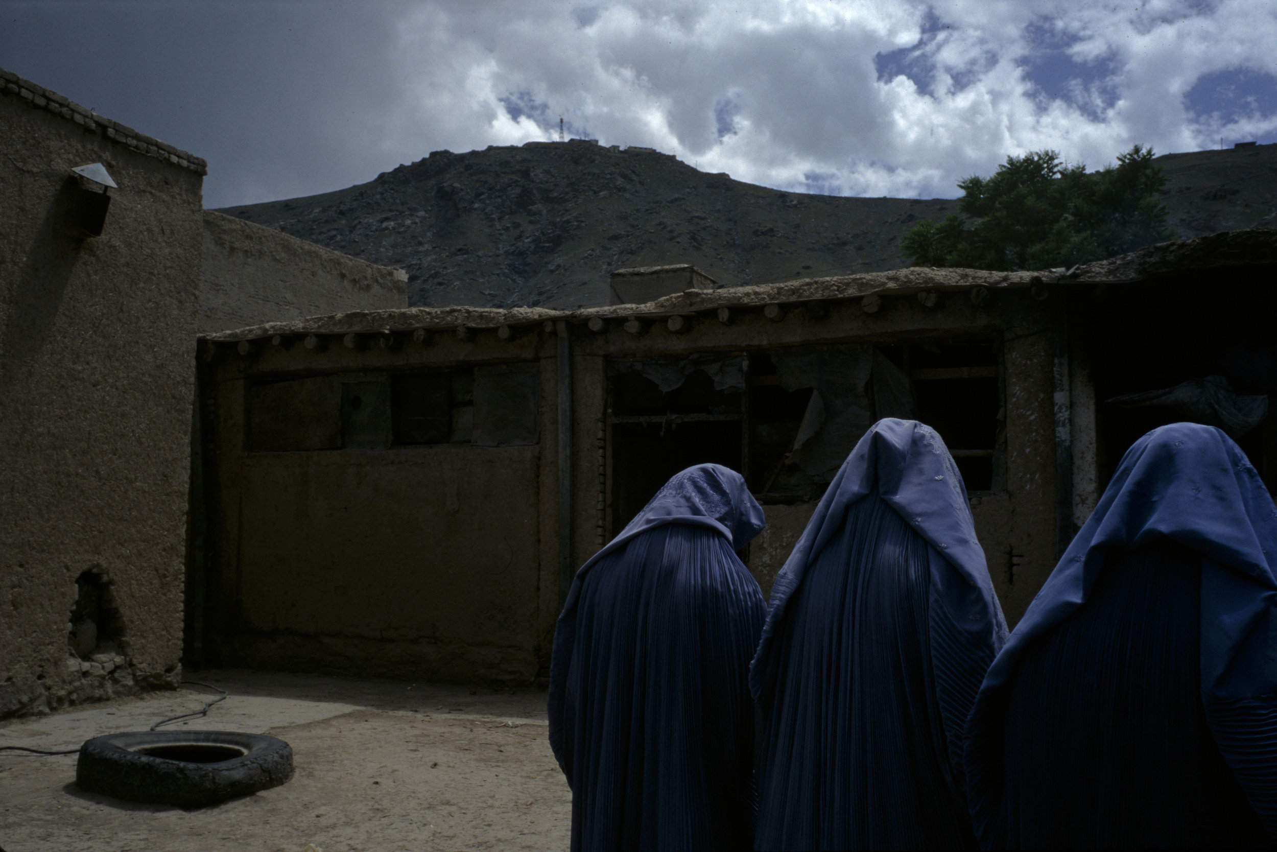 Three women near the entrance to a woman's bakery in Kabul, one of the few places permitted for women to gather and make money under the Taliban rule in Kabul.  The bakeries were operated by the World Food Program.