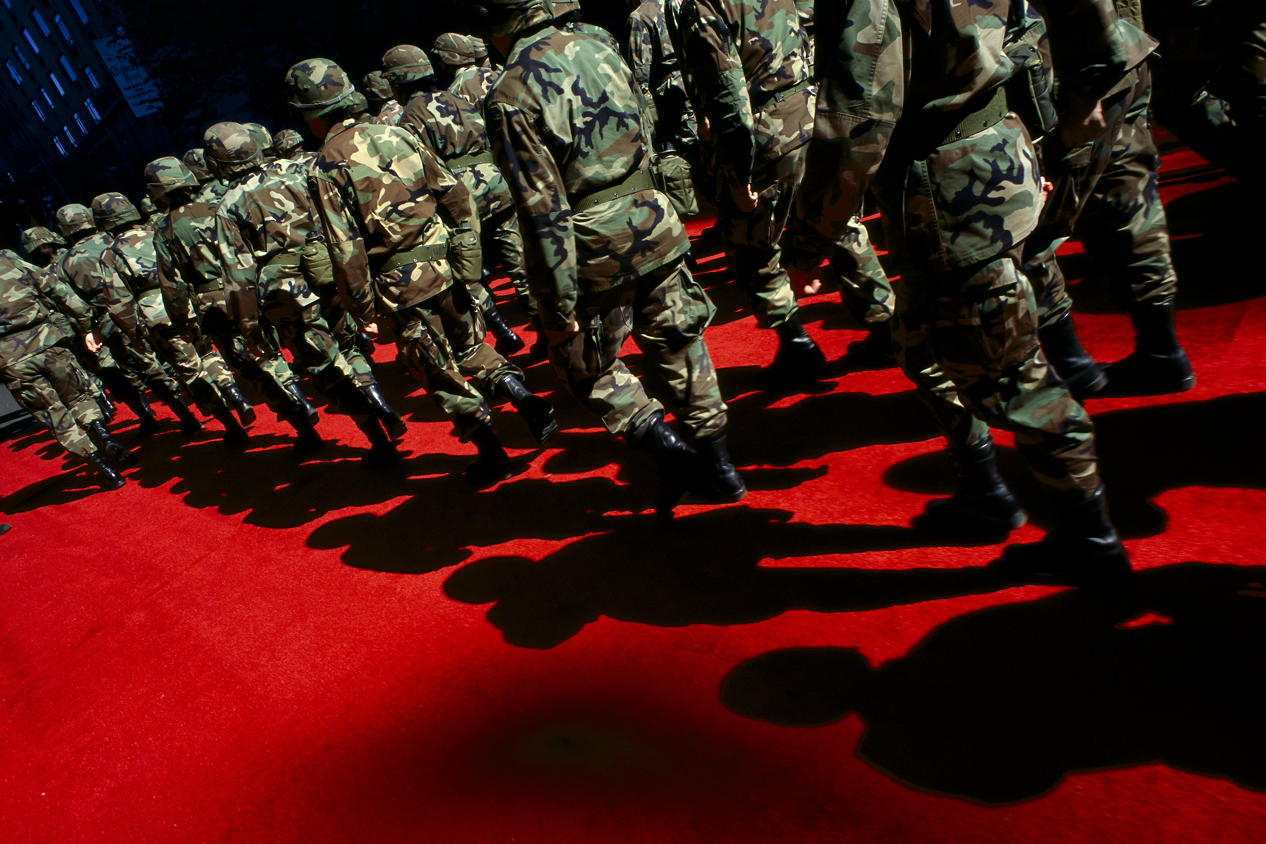 Soldiers march on a red carpet in a New York City Christopher Columbus parade, during the first days of the invasion of Afghanistan. New York 2001