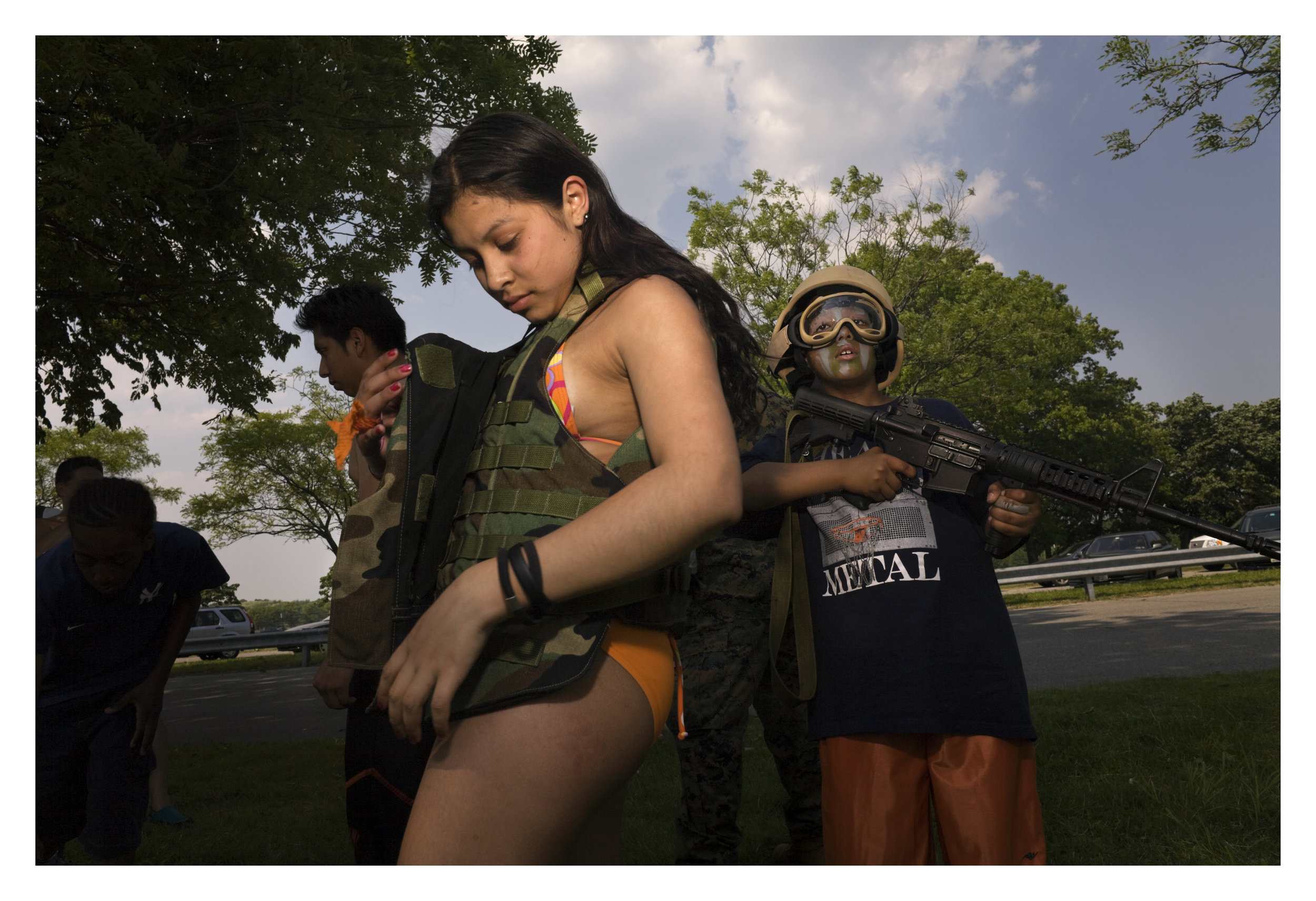 Marines land attack helicopters, paint children in camouflage and unfurl infantry weapons, including pistols with silencers for the public's amusement with the unspoken aim of recruiting new marines.     Orchard Beach,  Bronx, NY  2007