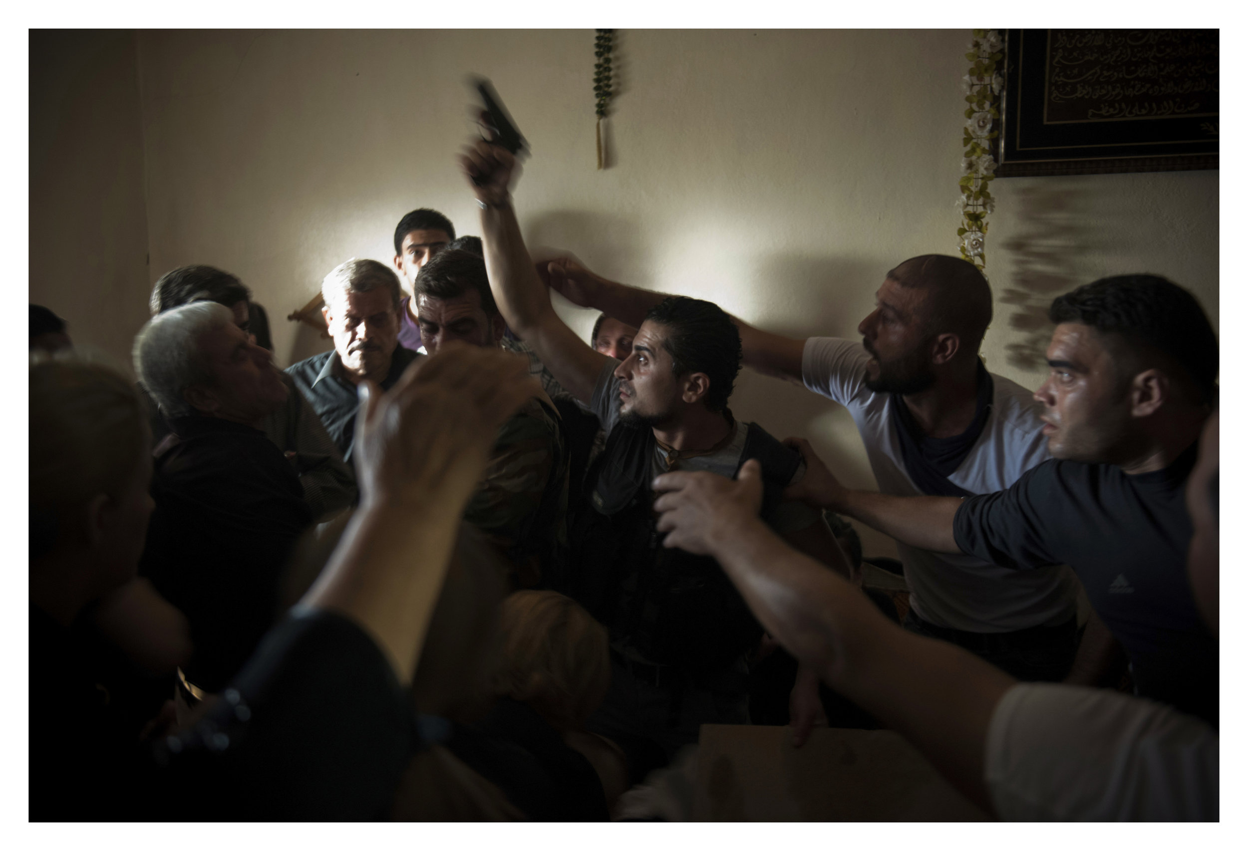 Bassel Barhoum (center) yells angrily after looking inside his brother's casket at his funeral in the village of Daqaqa in Latakia Province, Syria. Abu Layth died while fighting as an officer in the Syrian Army.