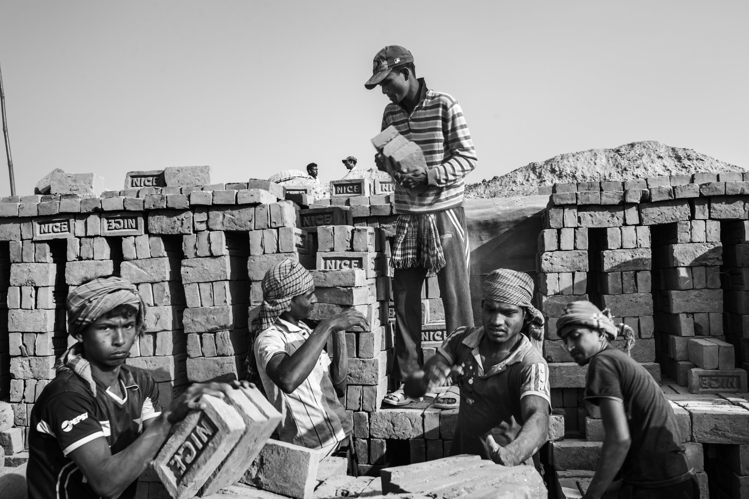 """Bangladesh, Rajshahi, January 2013, Children working with adults at """"Nice"""" brick factory. Their work is to stack bricks: for every 1000 bricks stacked, they get 20 Taka."""