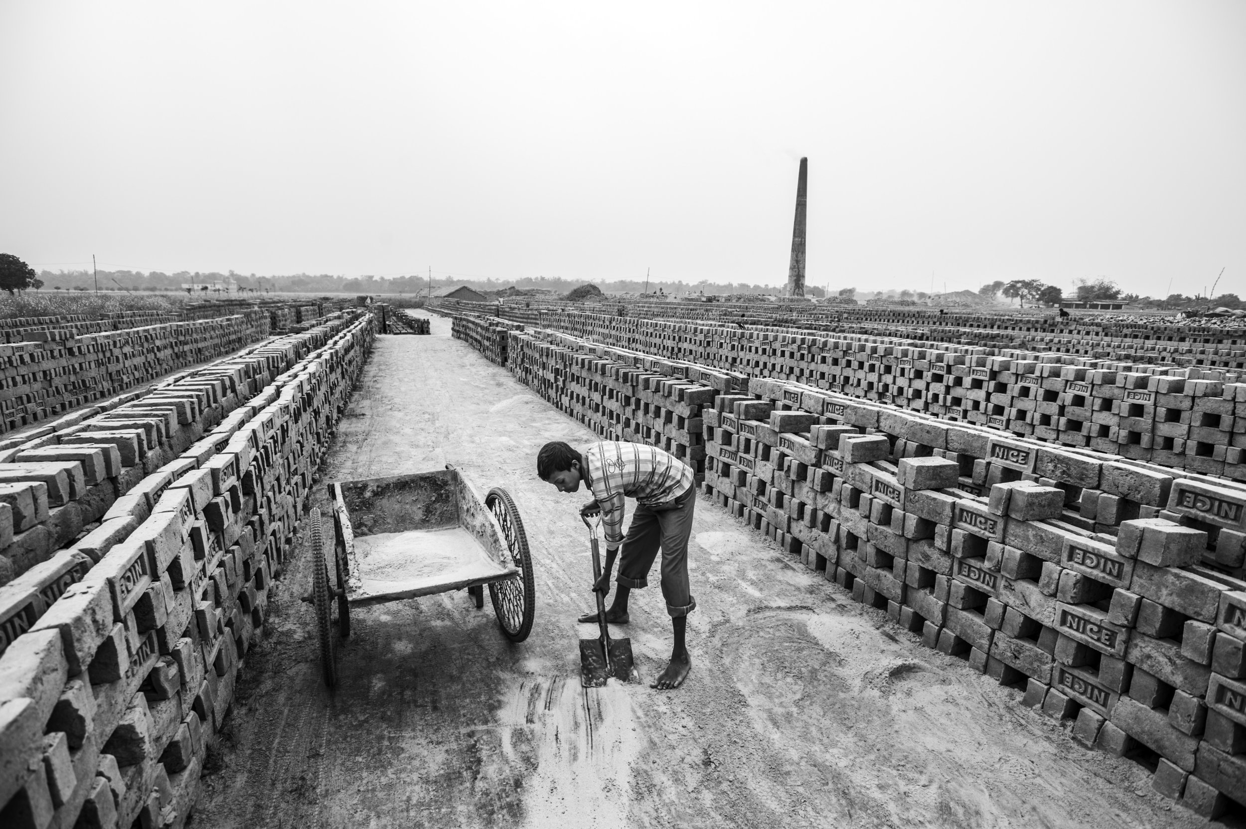 """Bangladesh, Rajshahi, January 2013, Rasel is eleven years old and works at """"Nice"""" brick factory. His work entails shifting and carting sand and mud from one place to another, as well as stacking bricks ."""